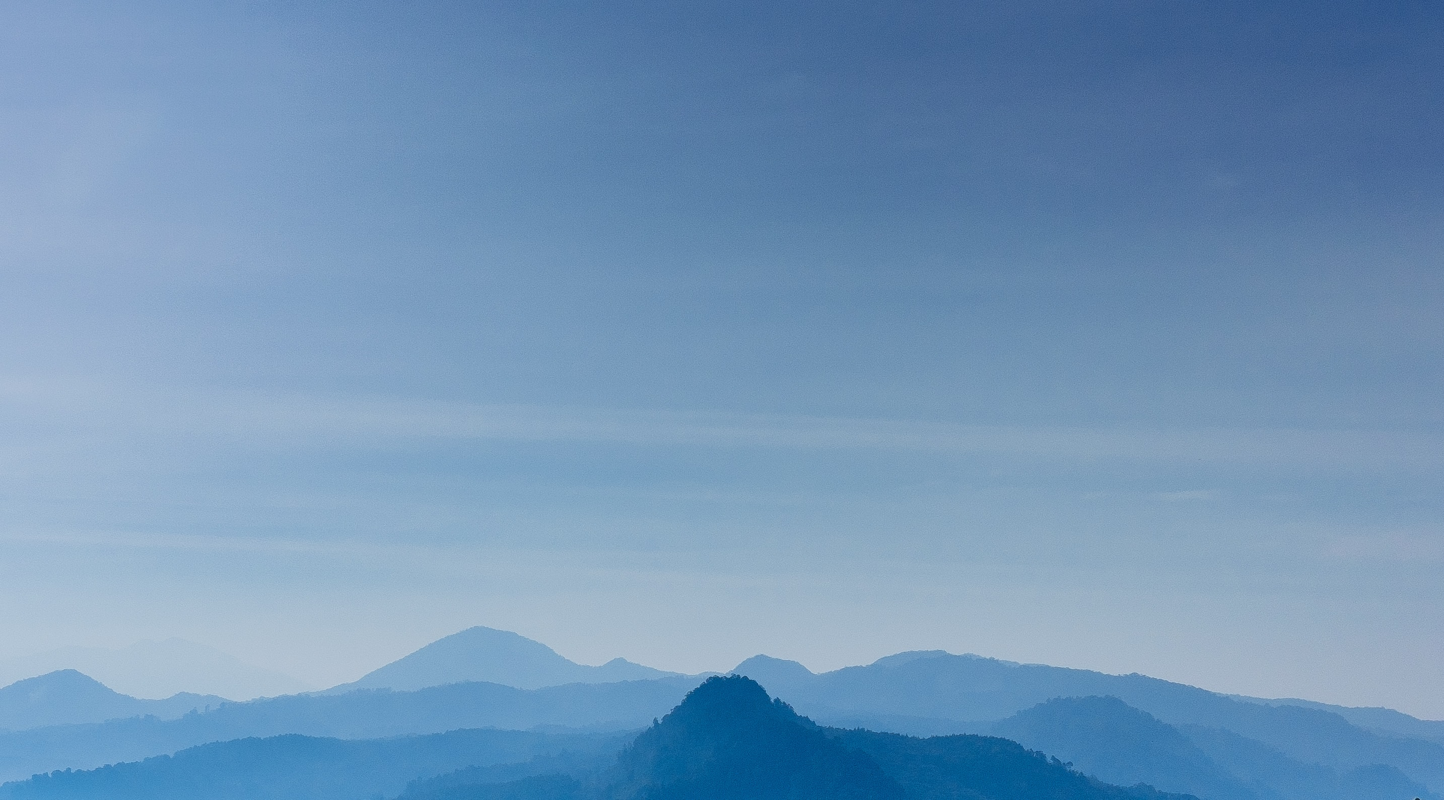 Pale silhouettes of mountain ridges  under a blue sky