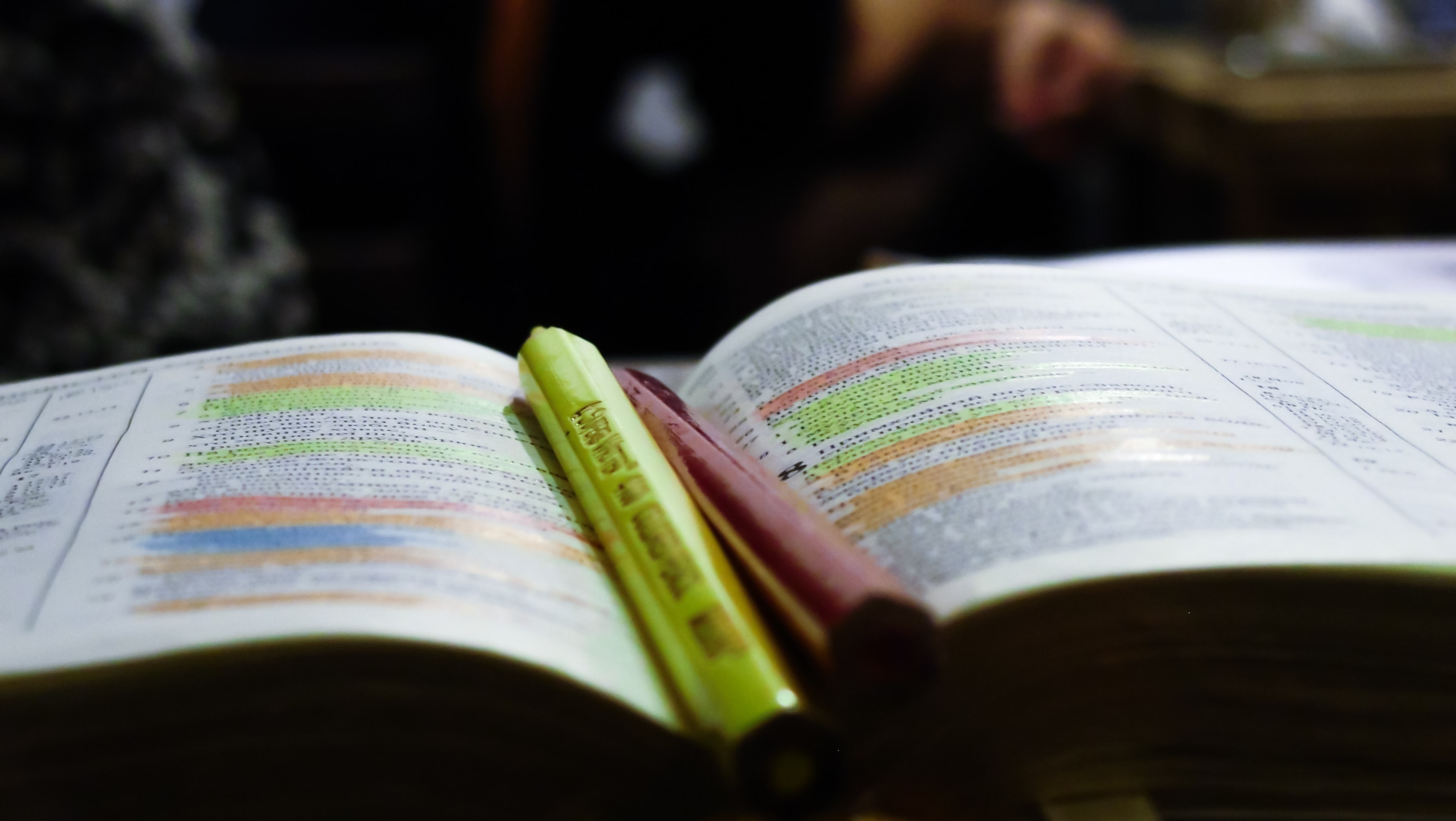 An open book with color highlighters in the middle.