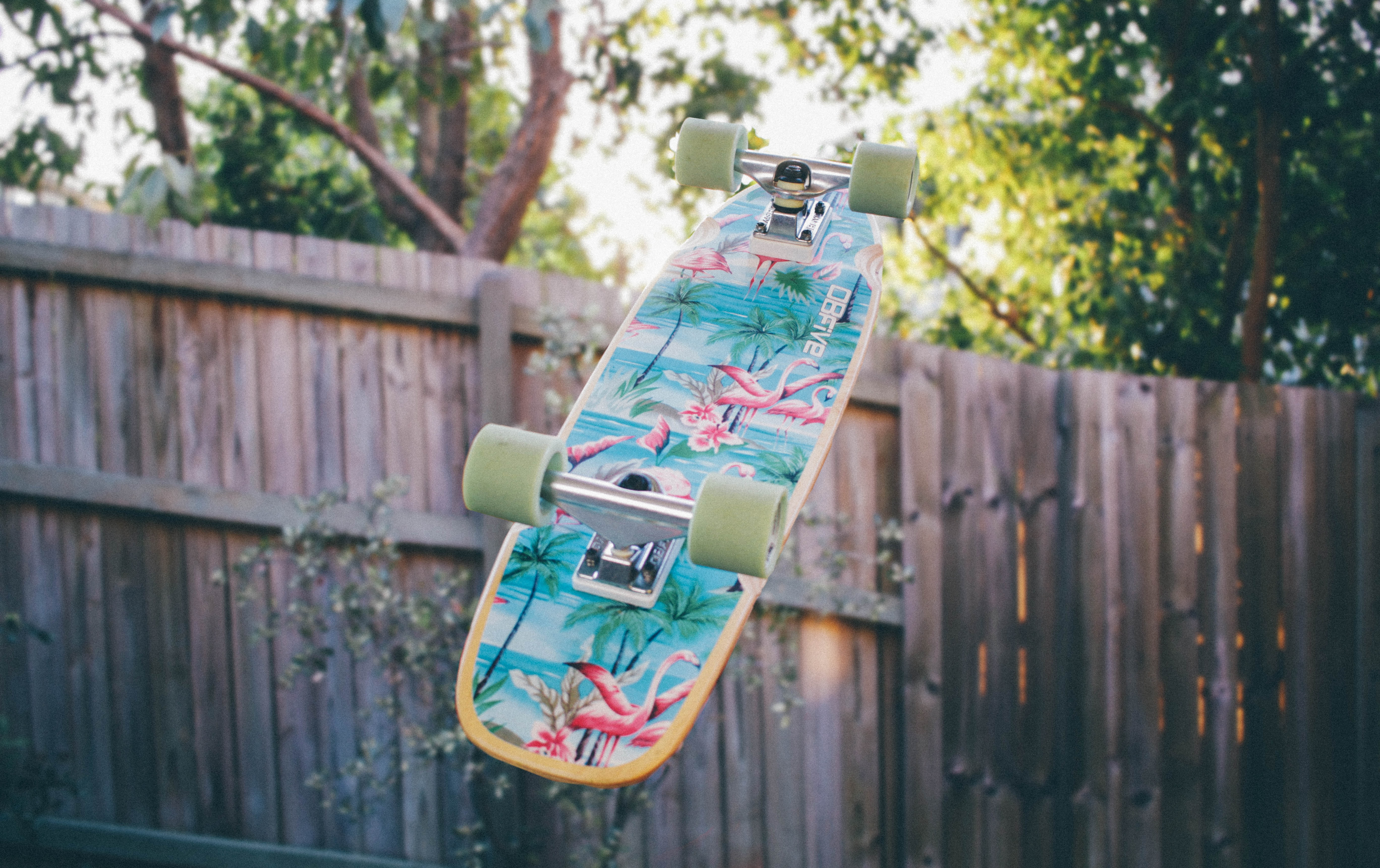 A colorful skateboard suspended in the air upside-down