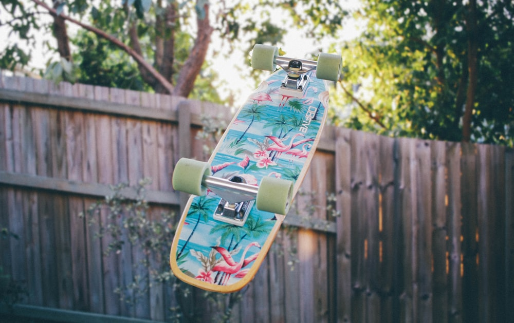skateboard flipped near wooden fence