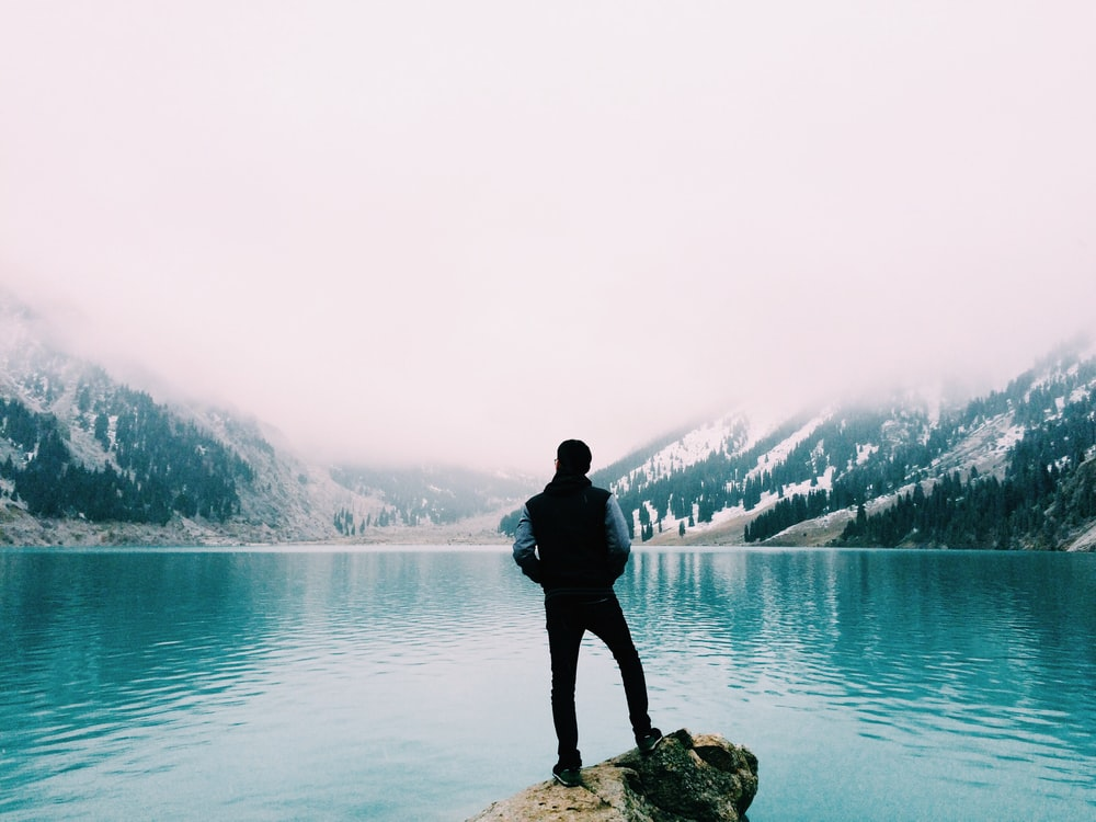 man standing on brown rock facing beside body of water