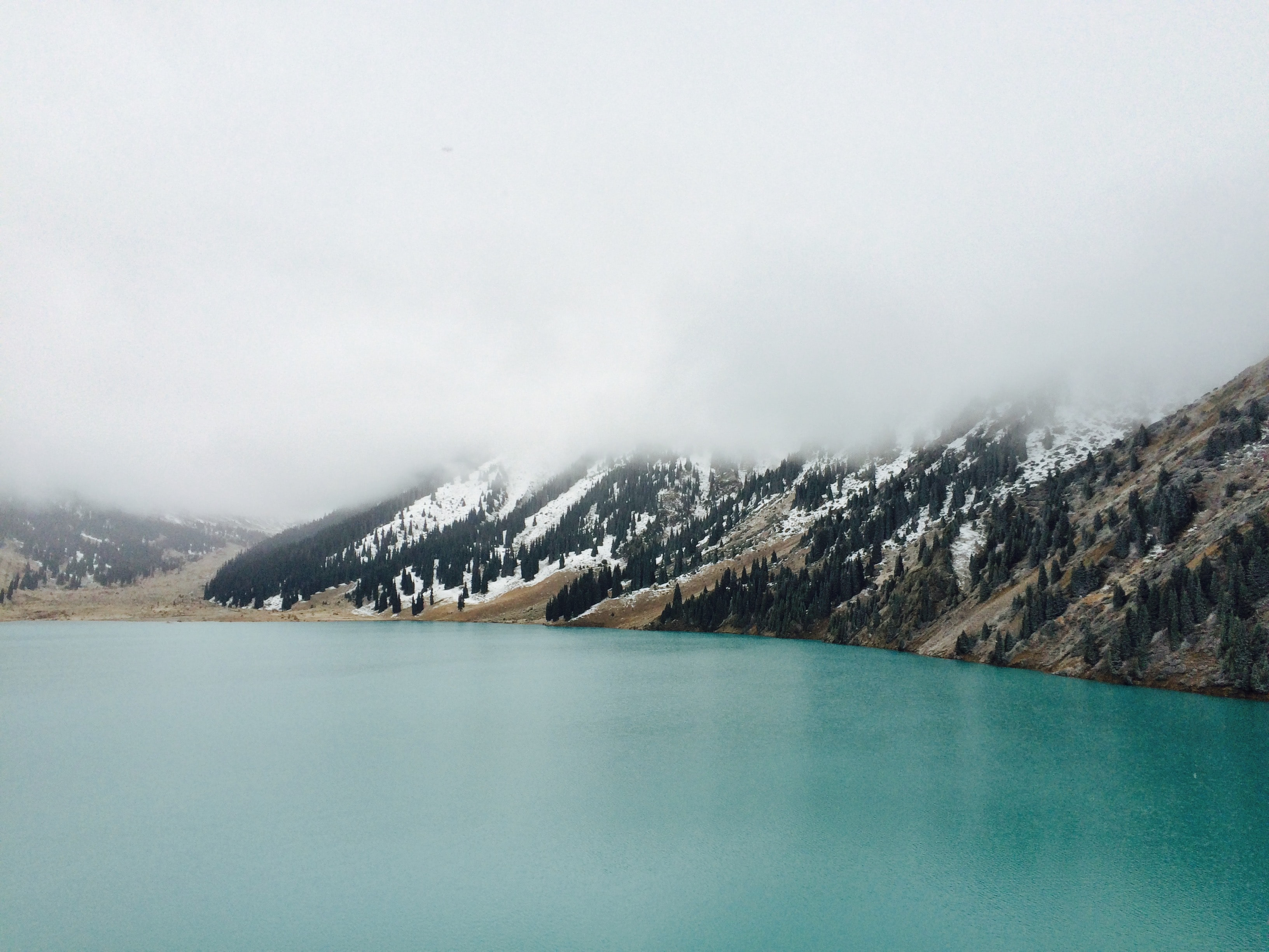 A mountain lake with snowy slopes covered in a thick layer of fog