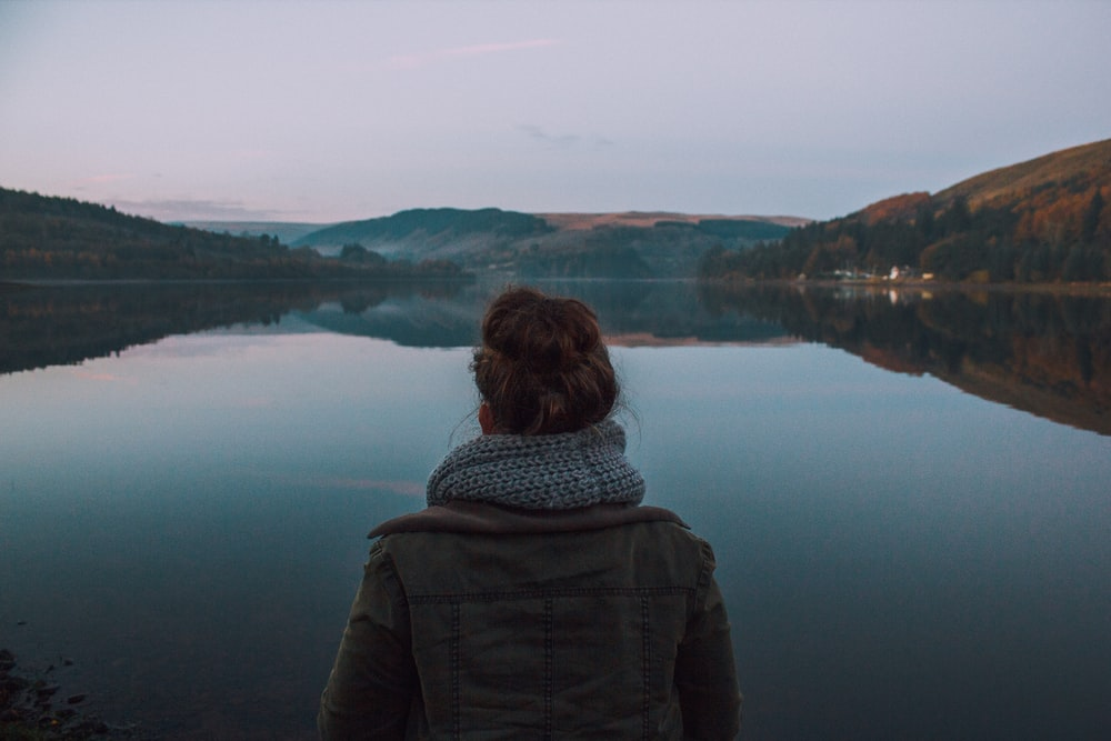 woman standing in front of body of water during dawn