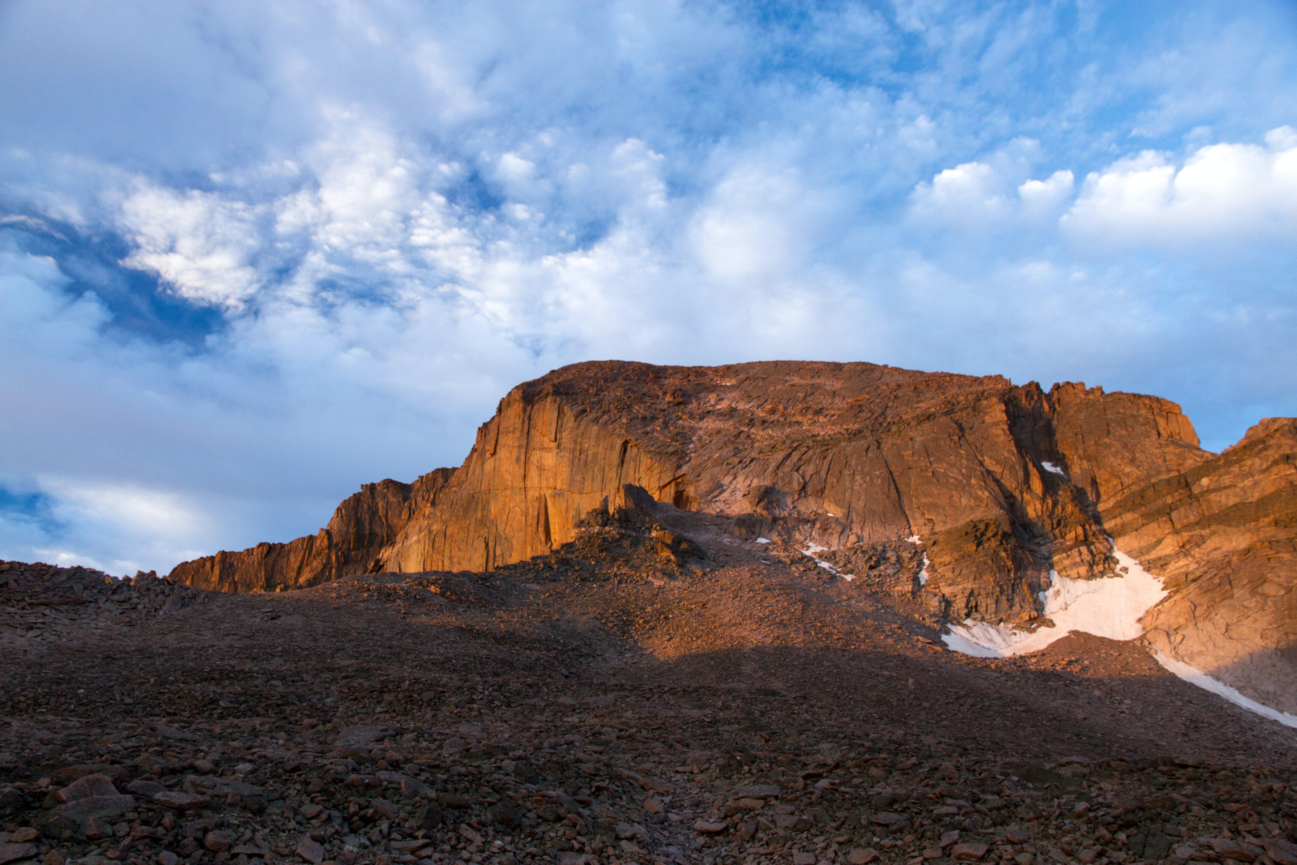 brown rock cliff under mid cloudy sky