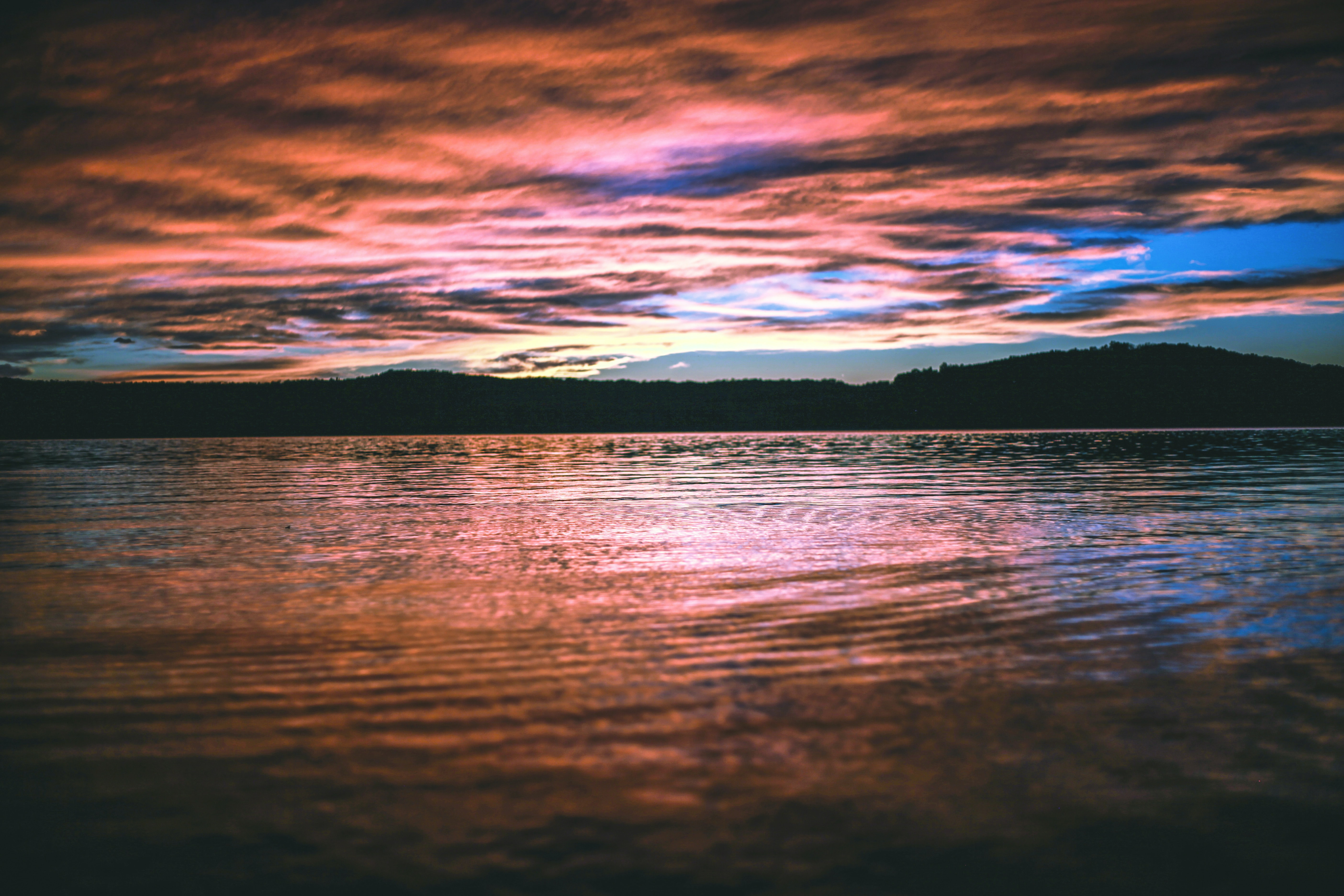 Pink clouds and deep blue sky reflected in water at sunset in Branson.
