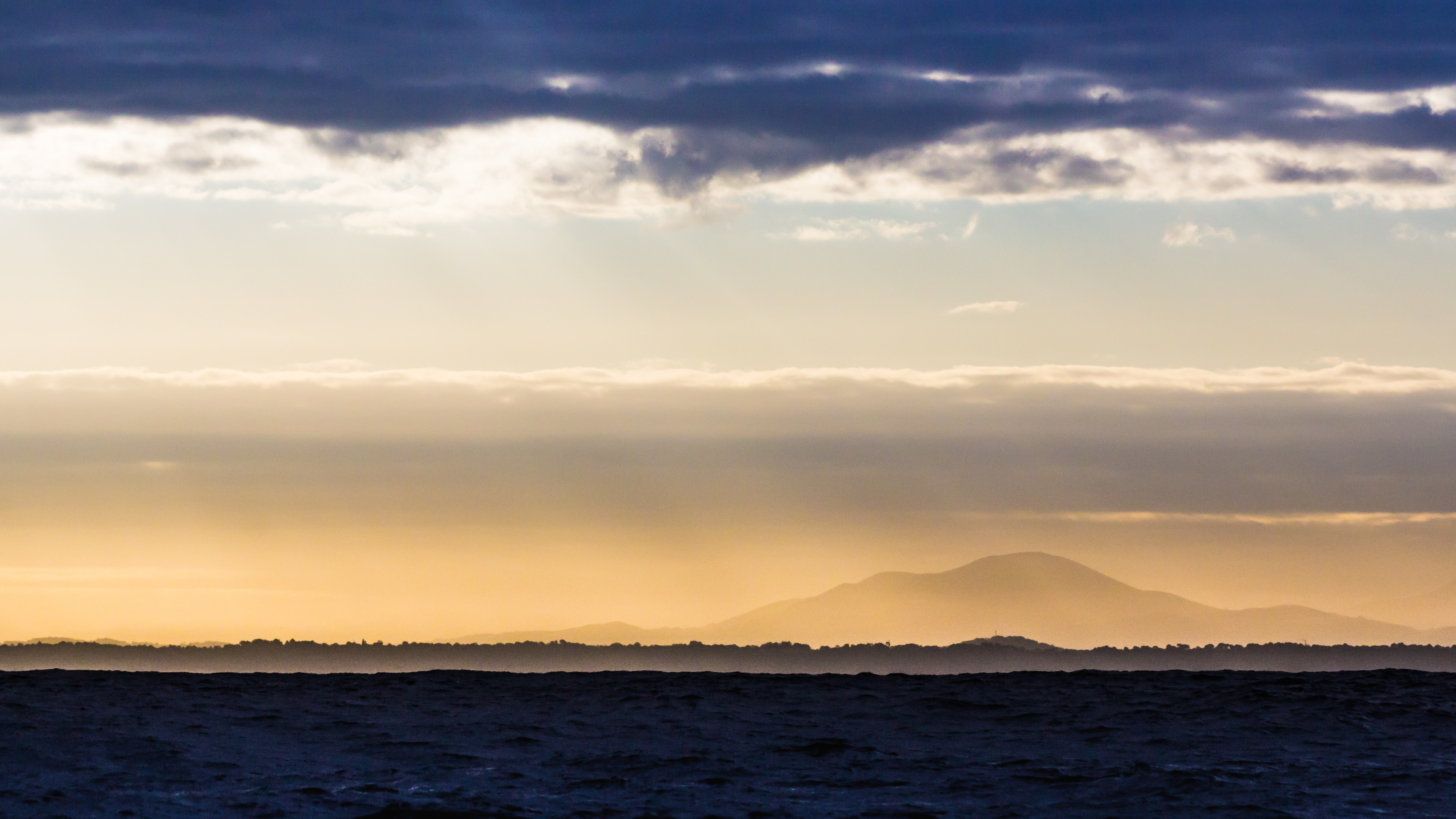 Silhouette of a mountain seen from the surface of a choppy sea during sunset