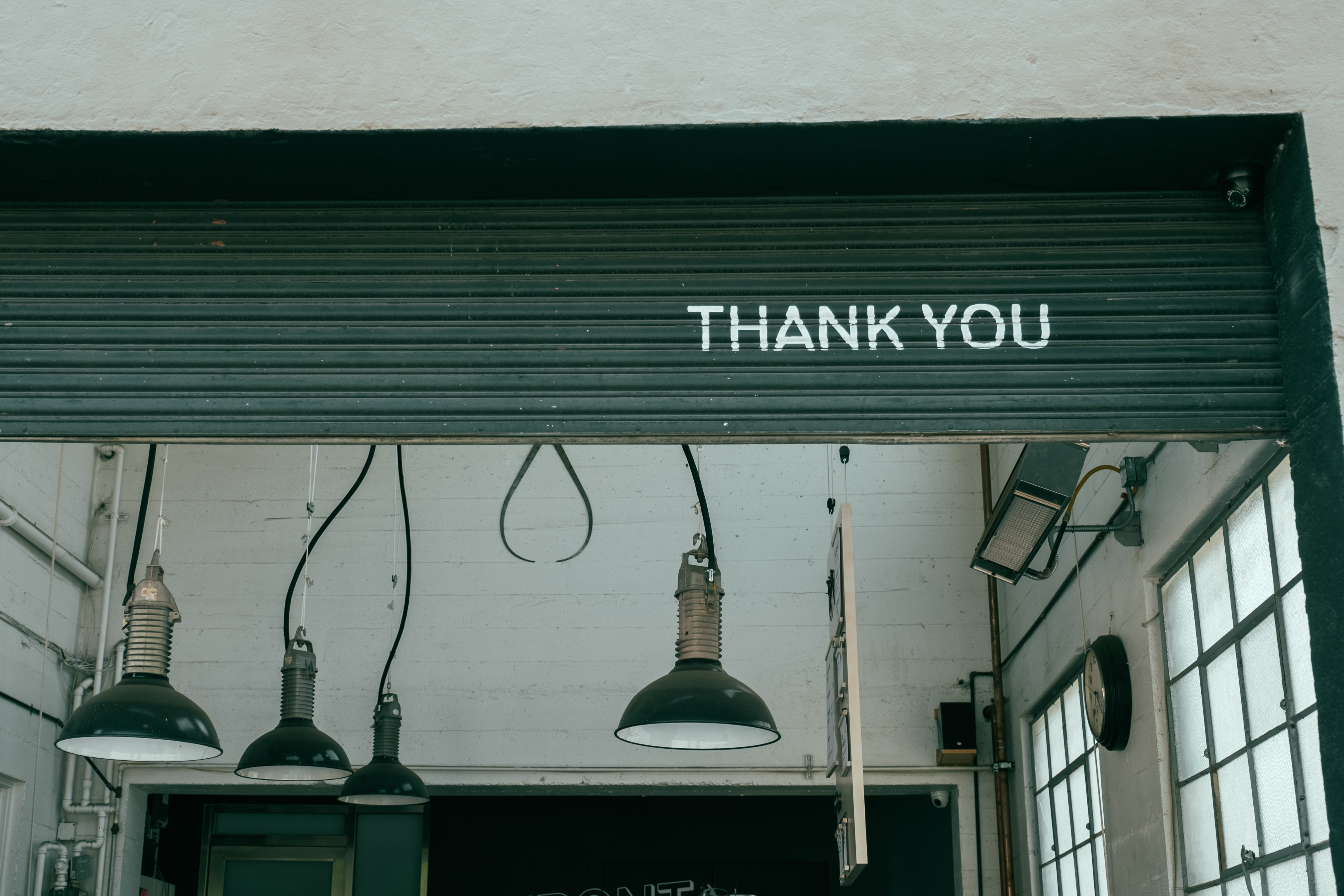 """""""Thank you"""" written on a roll-up wall in an industrial building"""