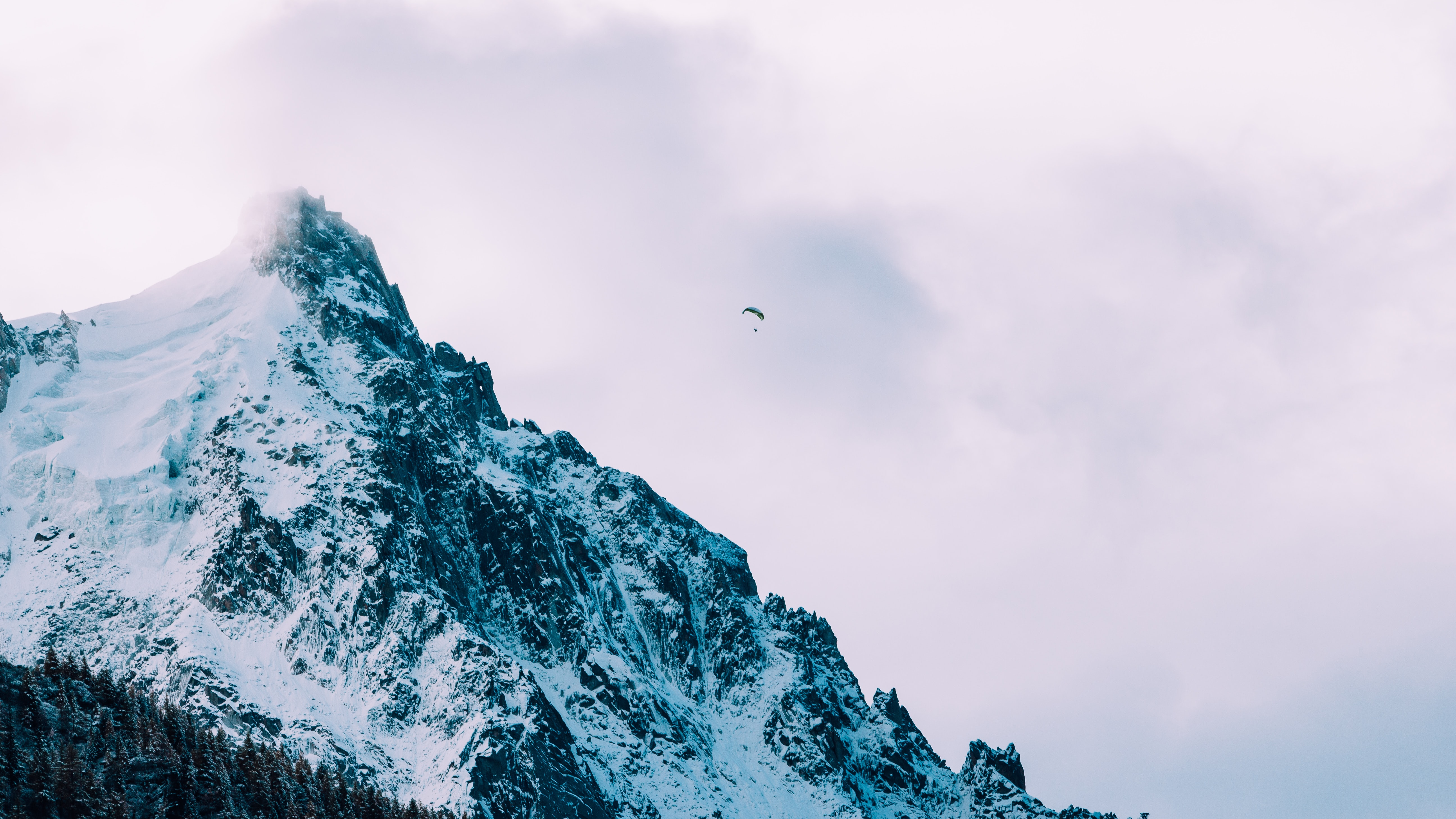 A paraglider in the sky over a snow-covered mountain