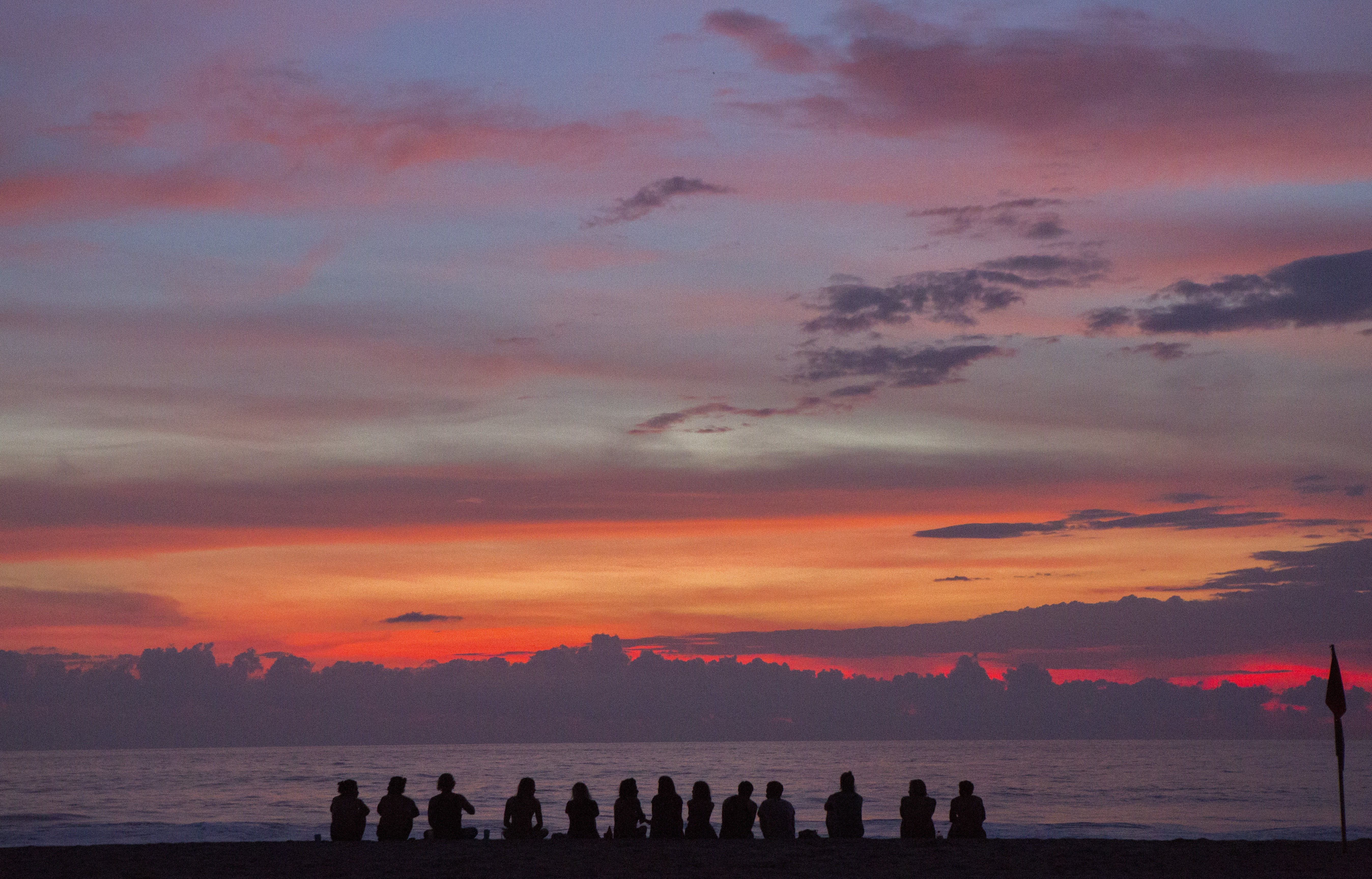 Thirteen people are silhouetted against a setting sun coloring the sky vibrantly