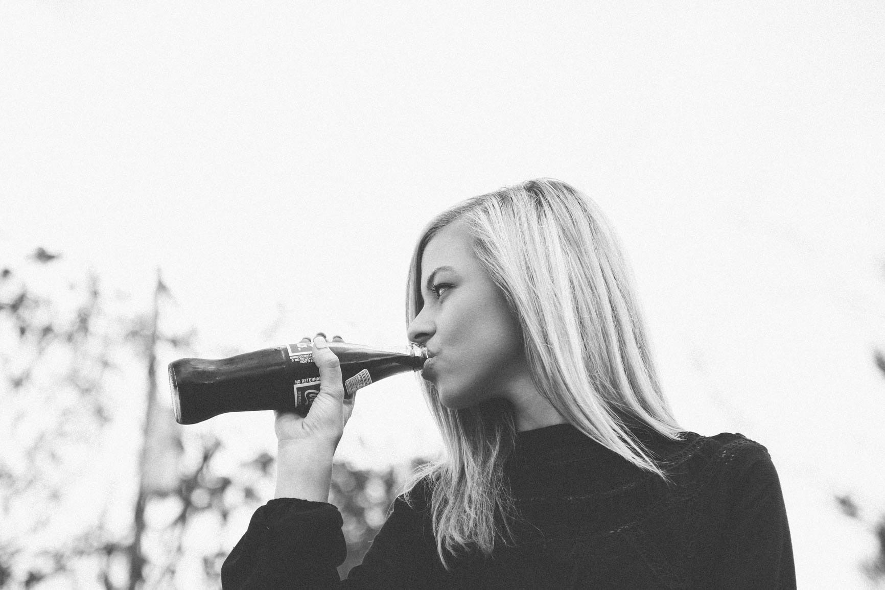Black and white shot of attractive blonde woman drinking cola from glass bottle
