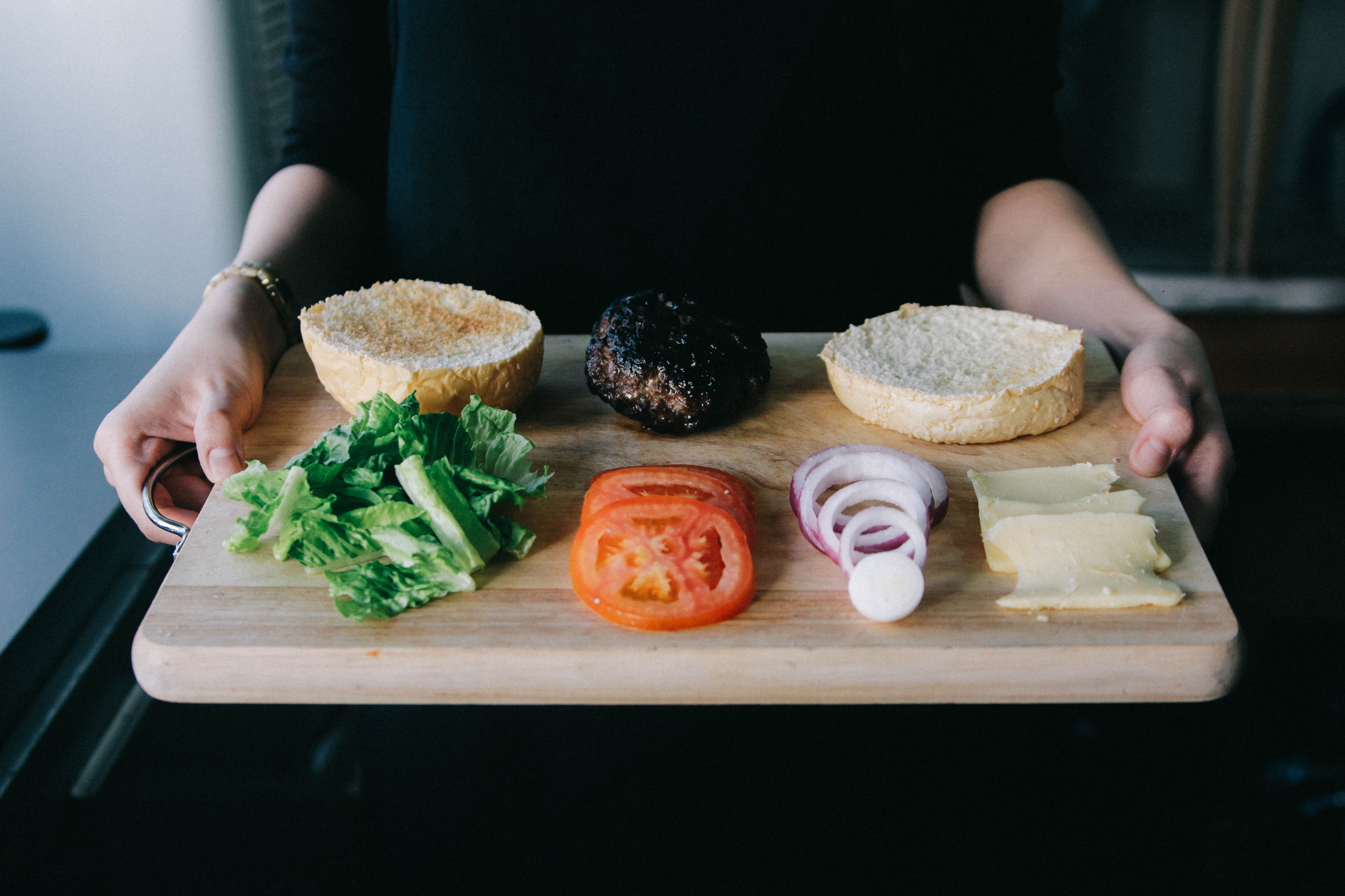 woman holding up wooden tray with lettuce, tomato, onions rings and cooked patty for burger