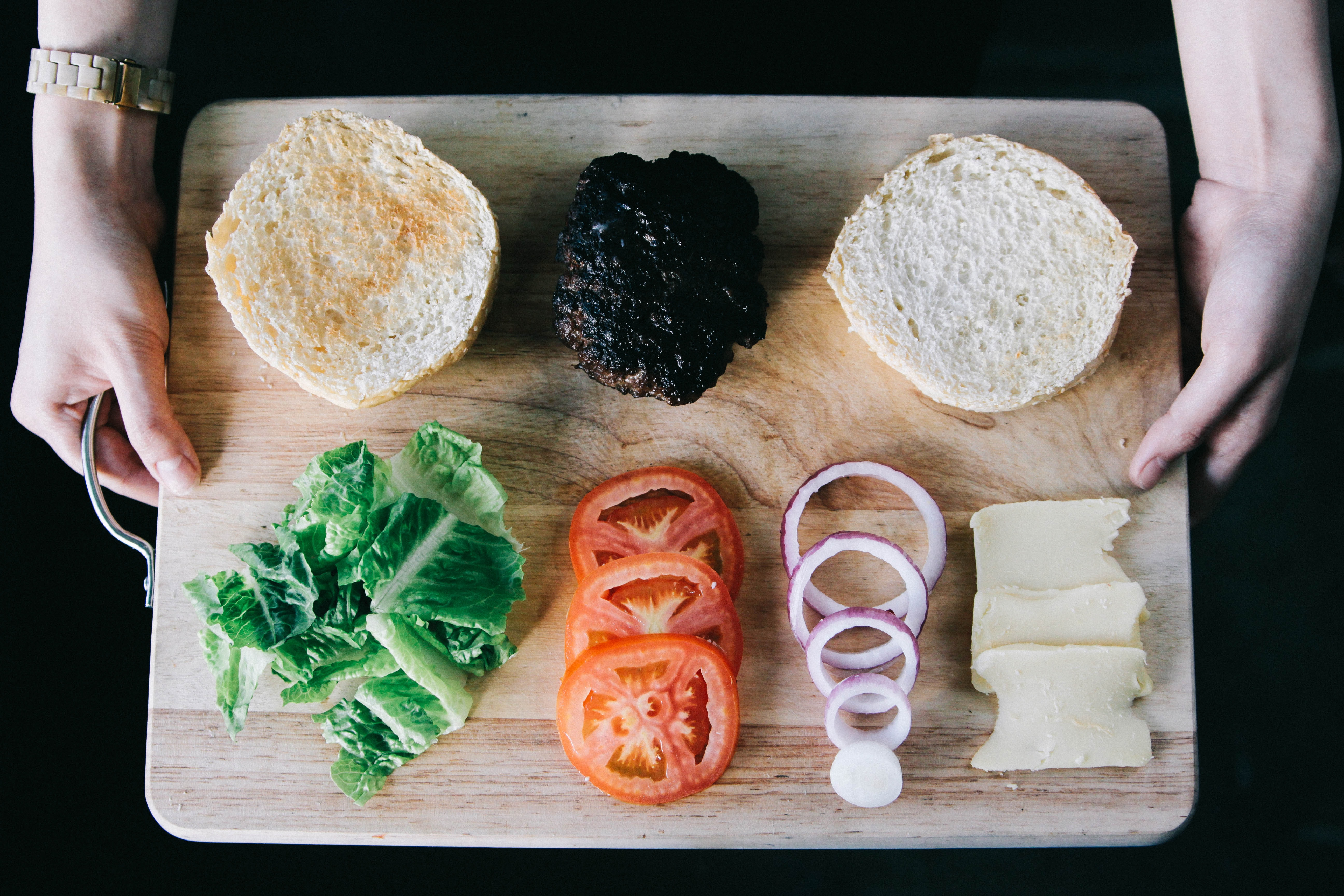 Neatly organized cutting board with hamburger, cheese, and vegetable fixings
