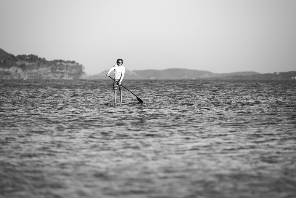 greyscale photo of man man on surfboard during daytime