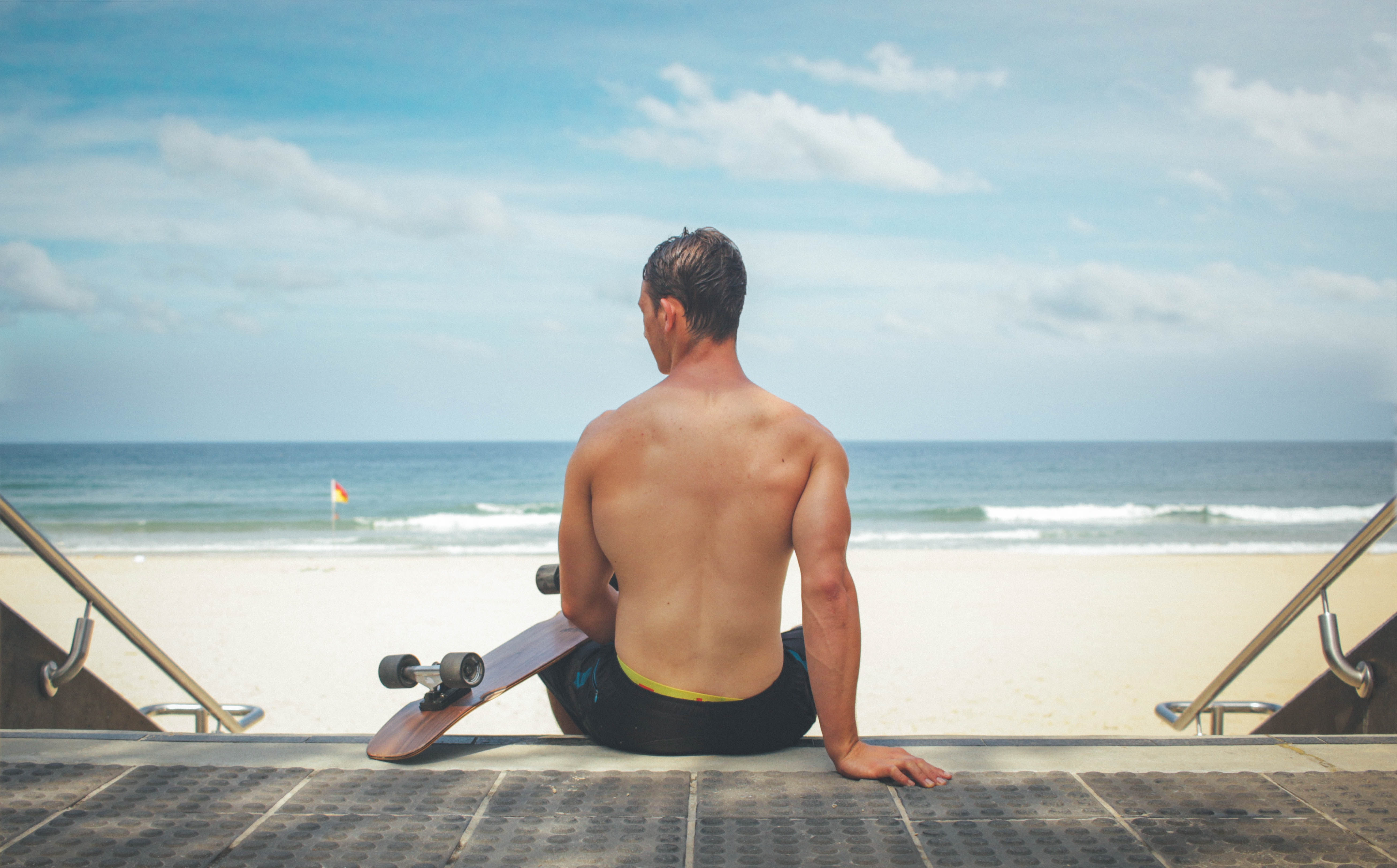 Muscular man sitting down to enjoy some quiet with his skateboard at Surfers paradise