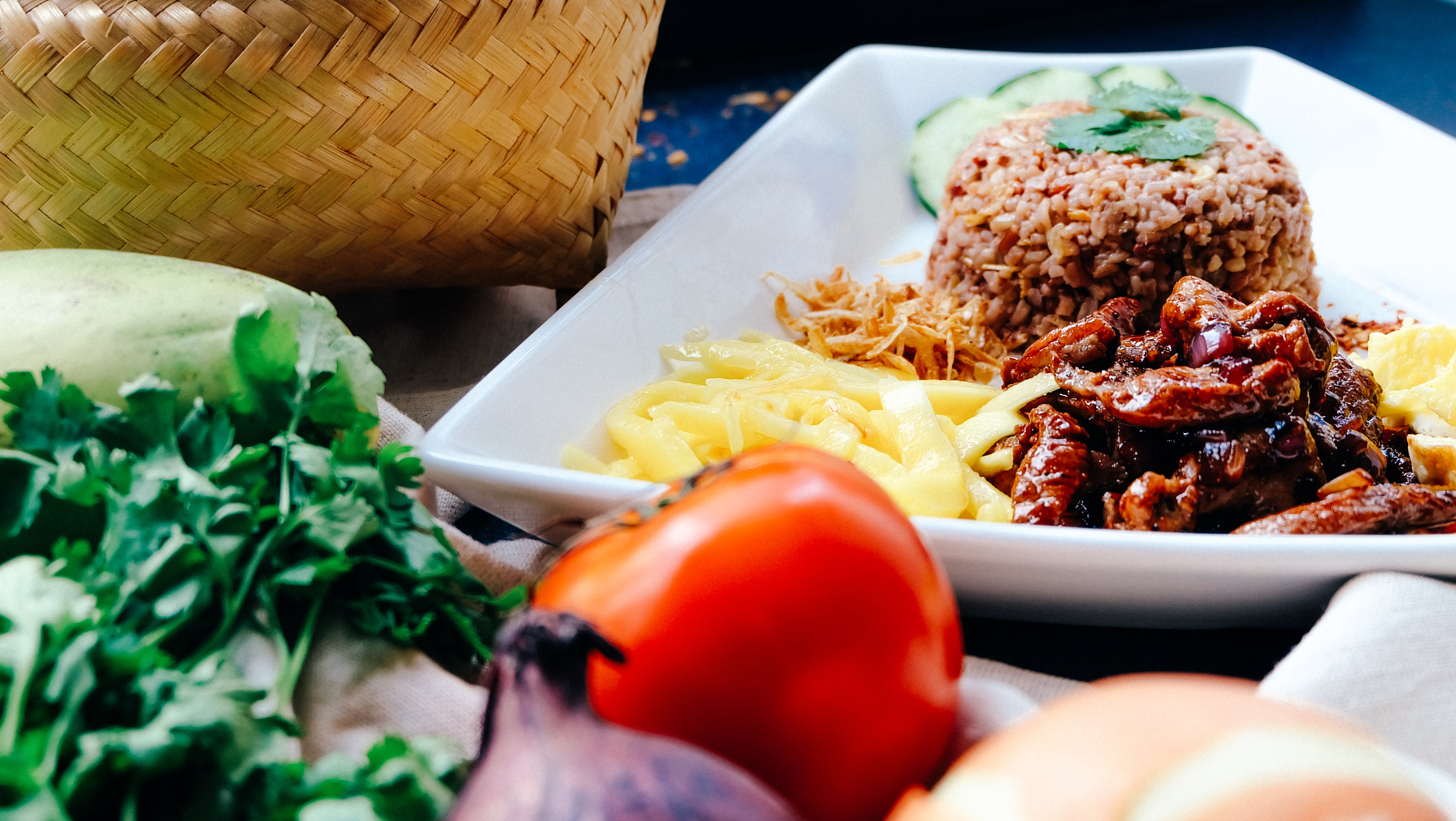 Rice, noodles, and, beef on a white plate with a tomato, onion, and herbs next to a whicker basket