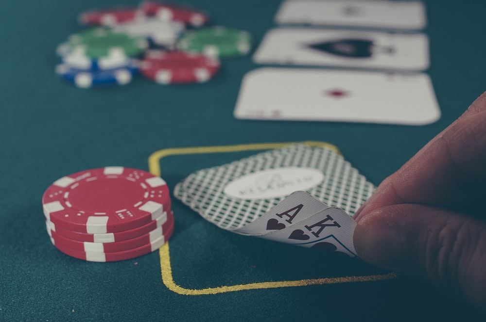 person holding black ace and king spades playing cards on poker table