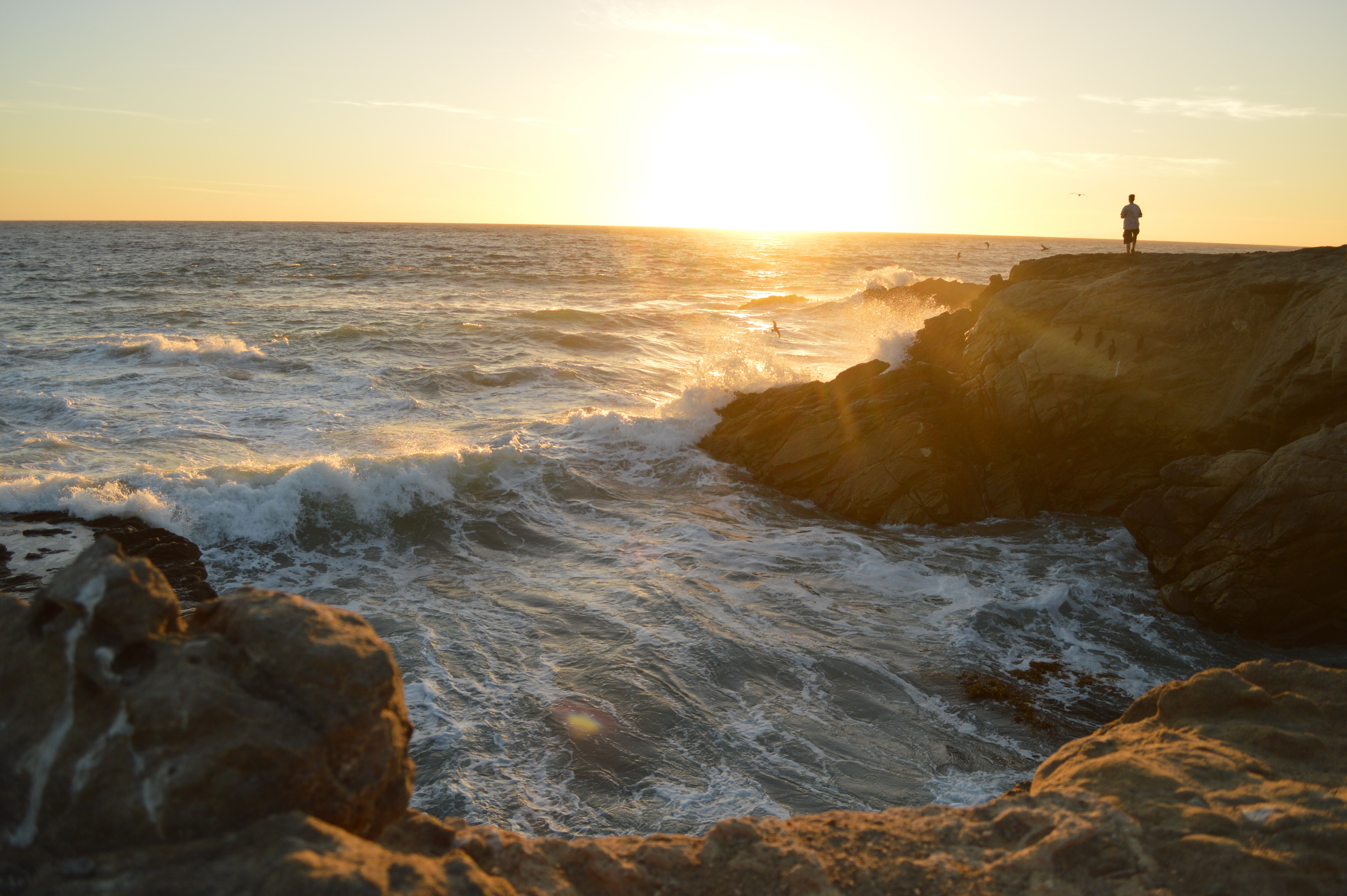 Man standing on a cliff by the ocean bay looking at the sunset at Leo Carrillo State Beach