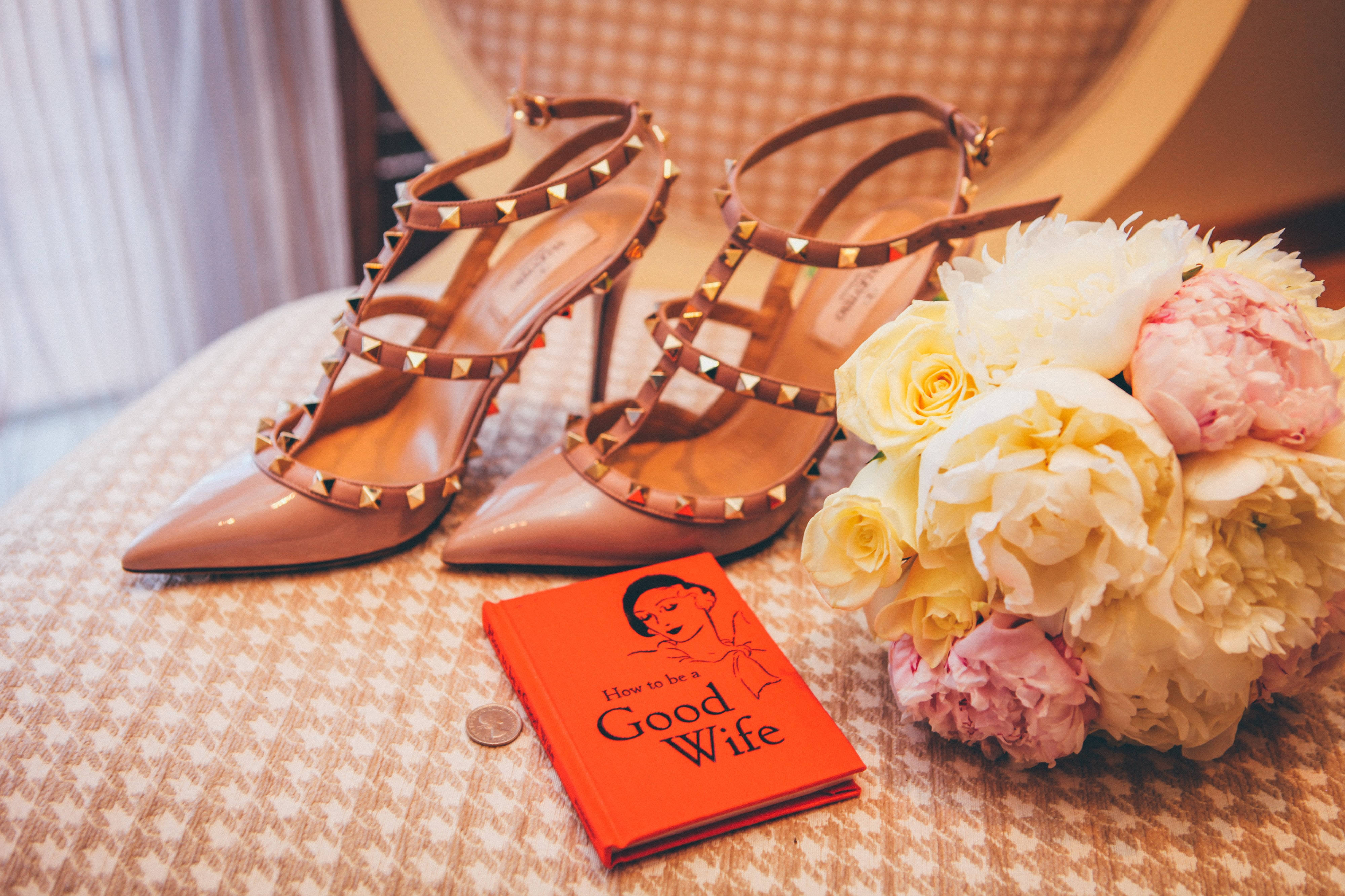 "Bride's chair with studded stilettos, rose bouquet, and book entitled ""How To Be A Good Wife"""