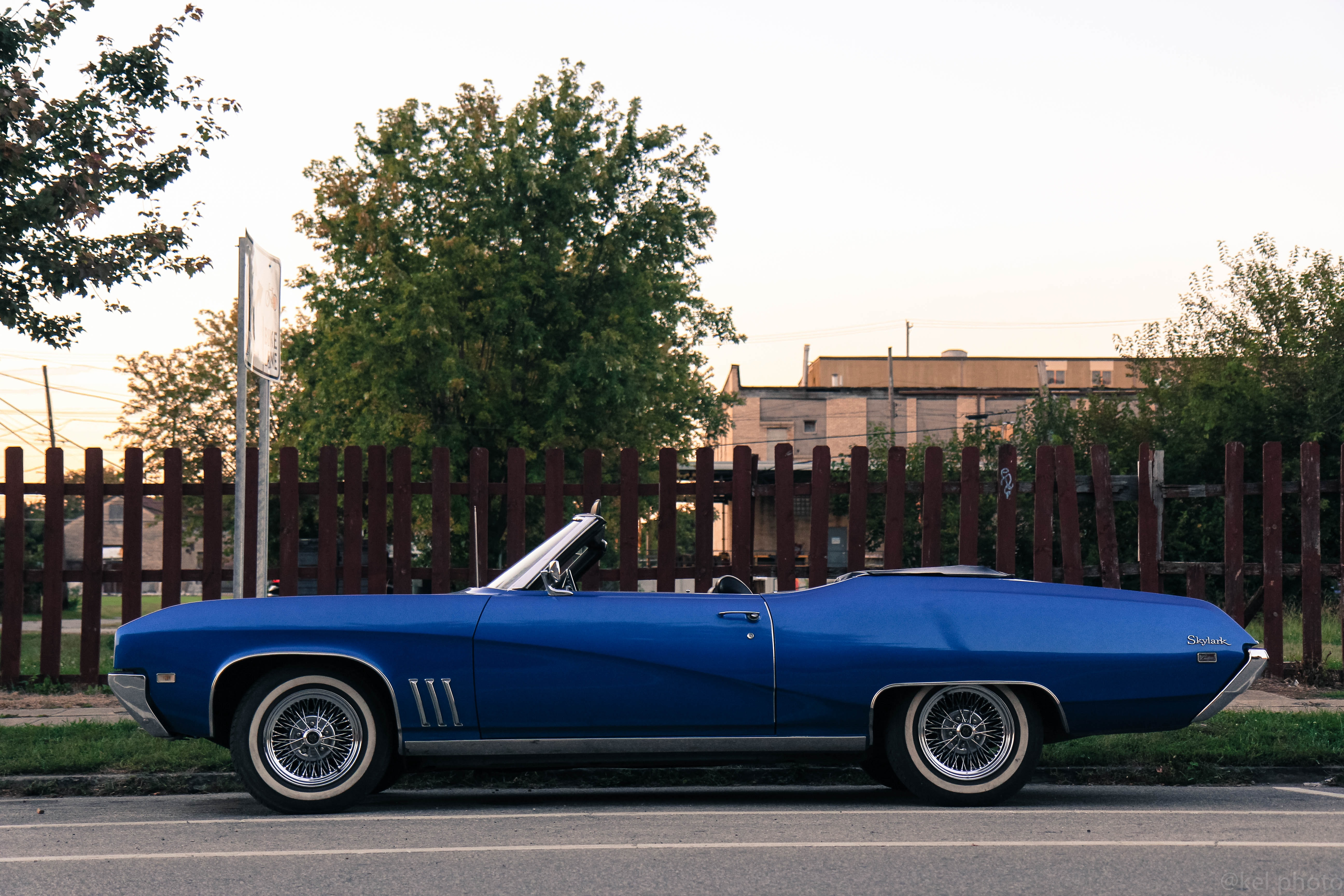 Blue convertible vehicle parked on pavement in front of brown picket fence, trees and building