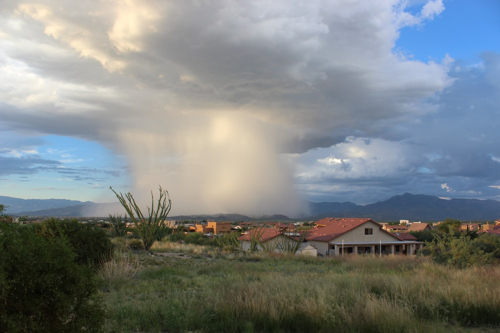 photo of cloud formation near houses during daytime