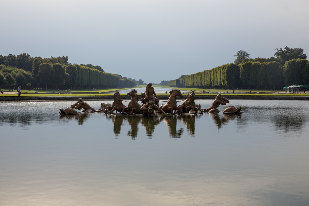 statue of horses on body of water at daytime