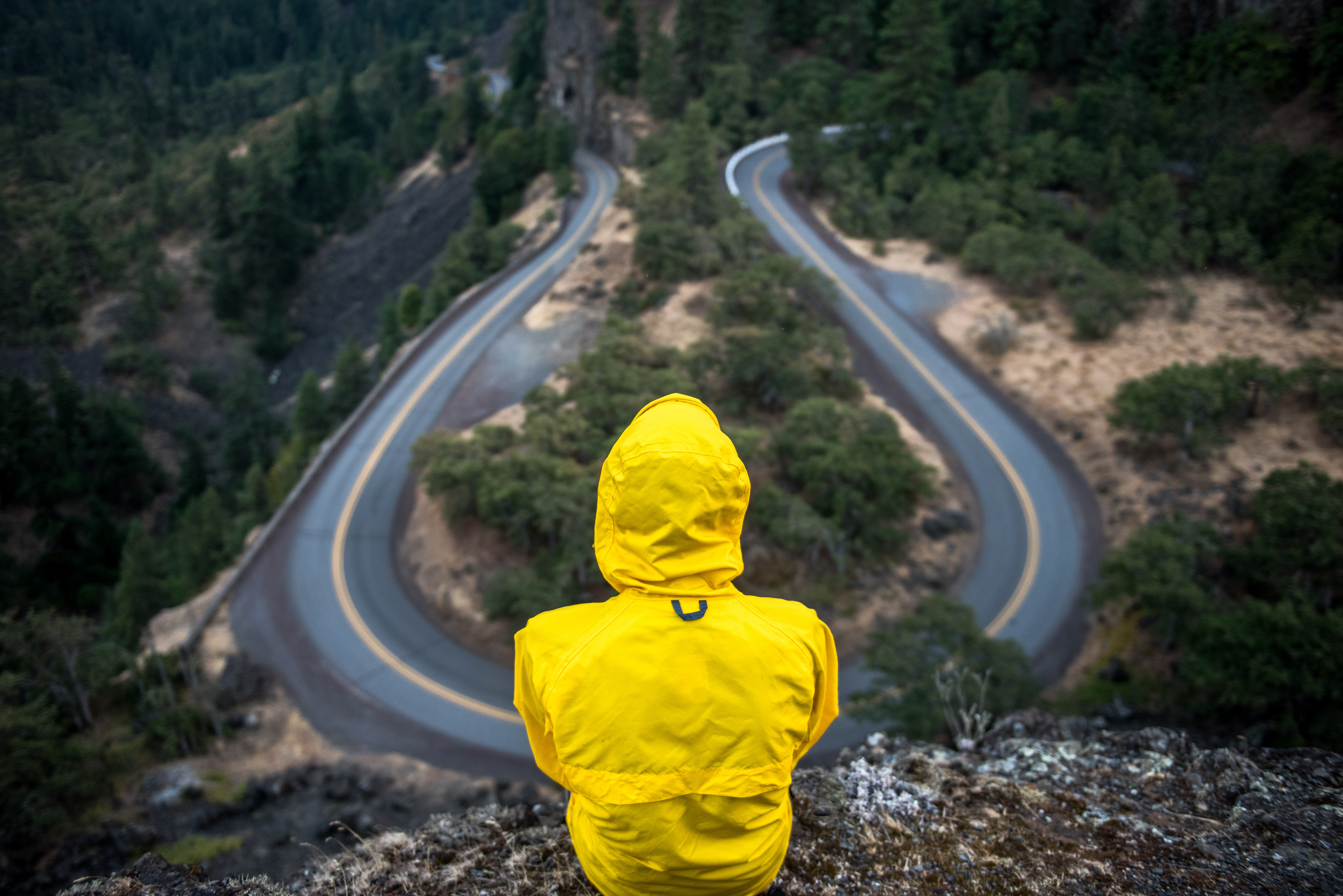 A person in a yellow jacket with a hood sitting on a rock over a U-turn in a road