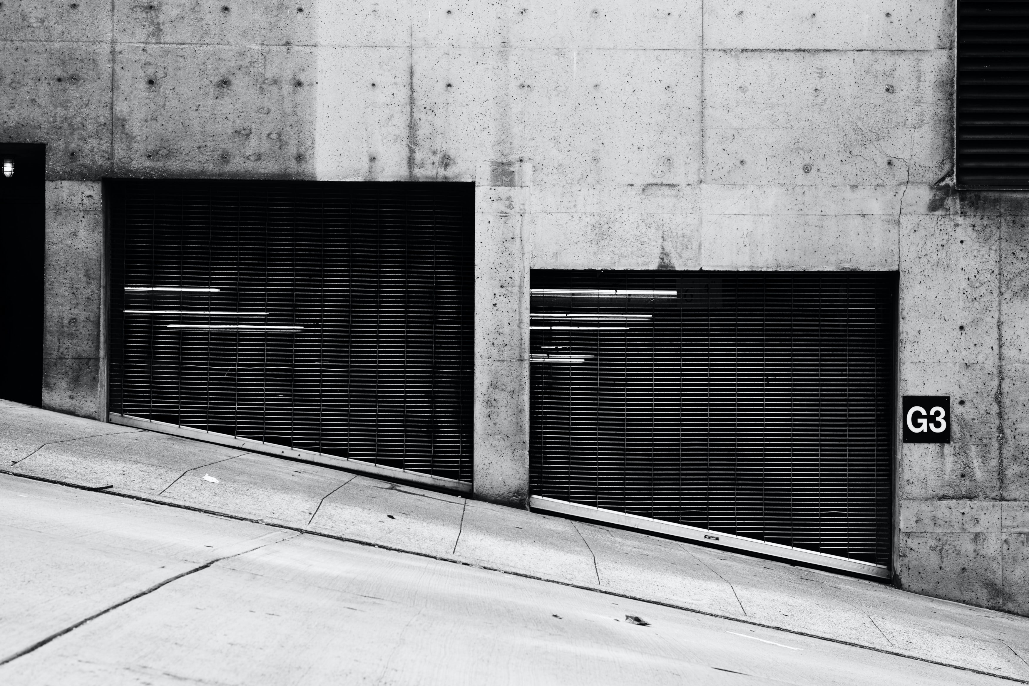 A black and white photograph of the entrance of a parking garage.