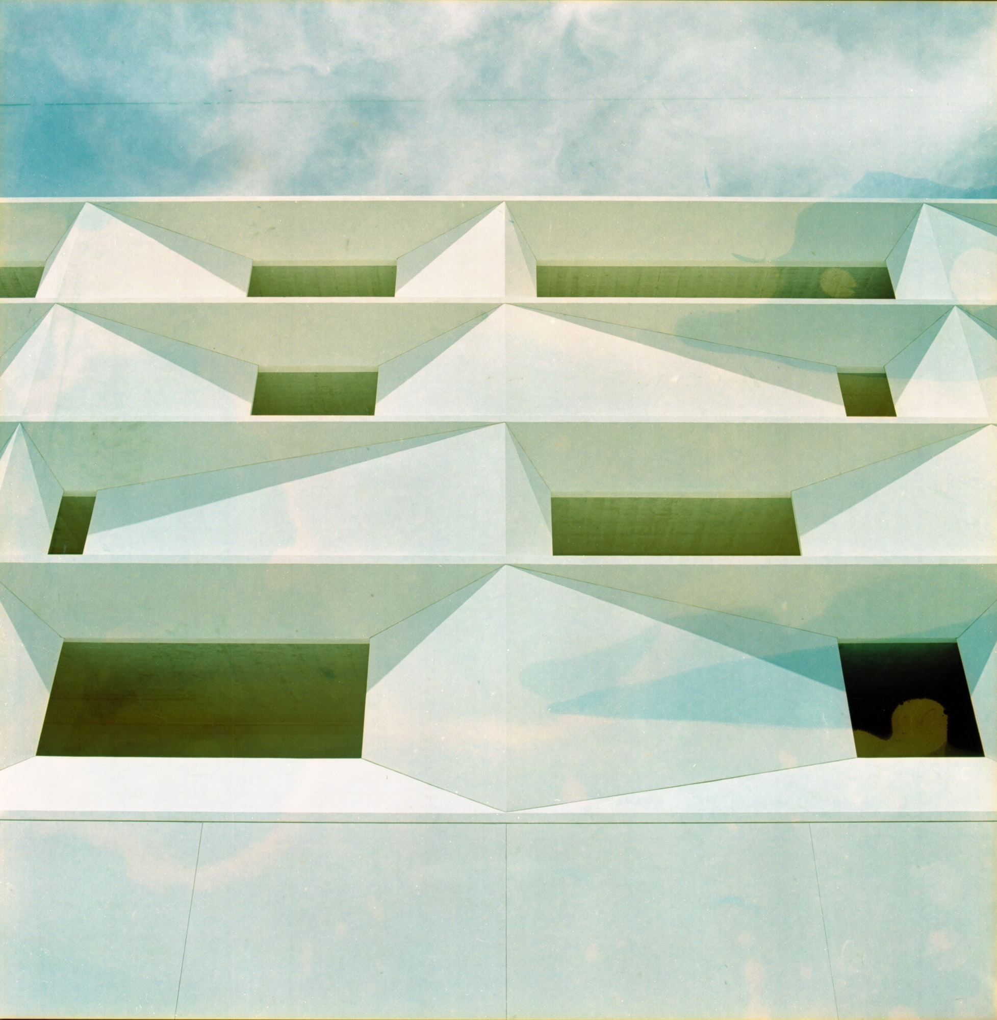 Modernist design white building with windows from below and blue sky with clouds