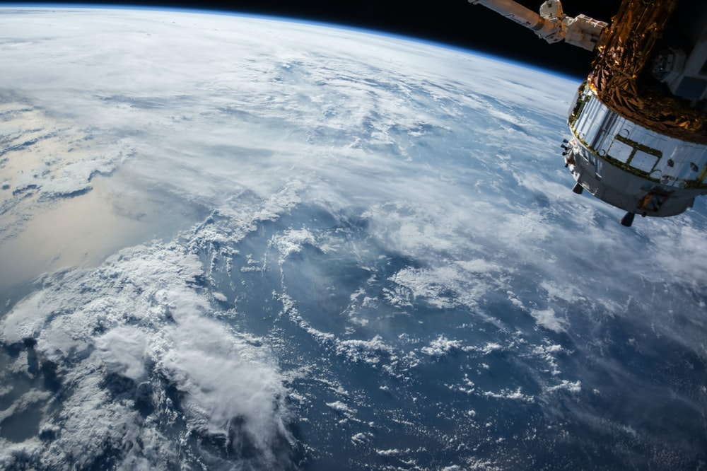 A View From The Orbit On An Artificial Satellite Over White Clouds Ocean