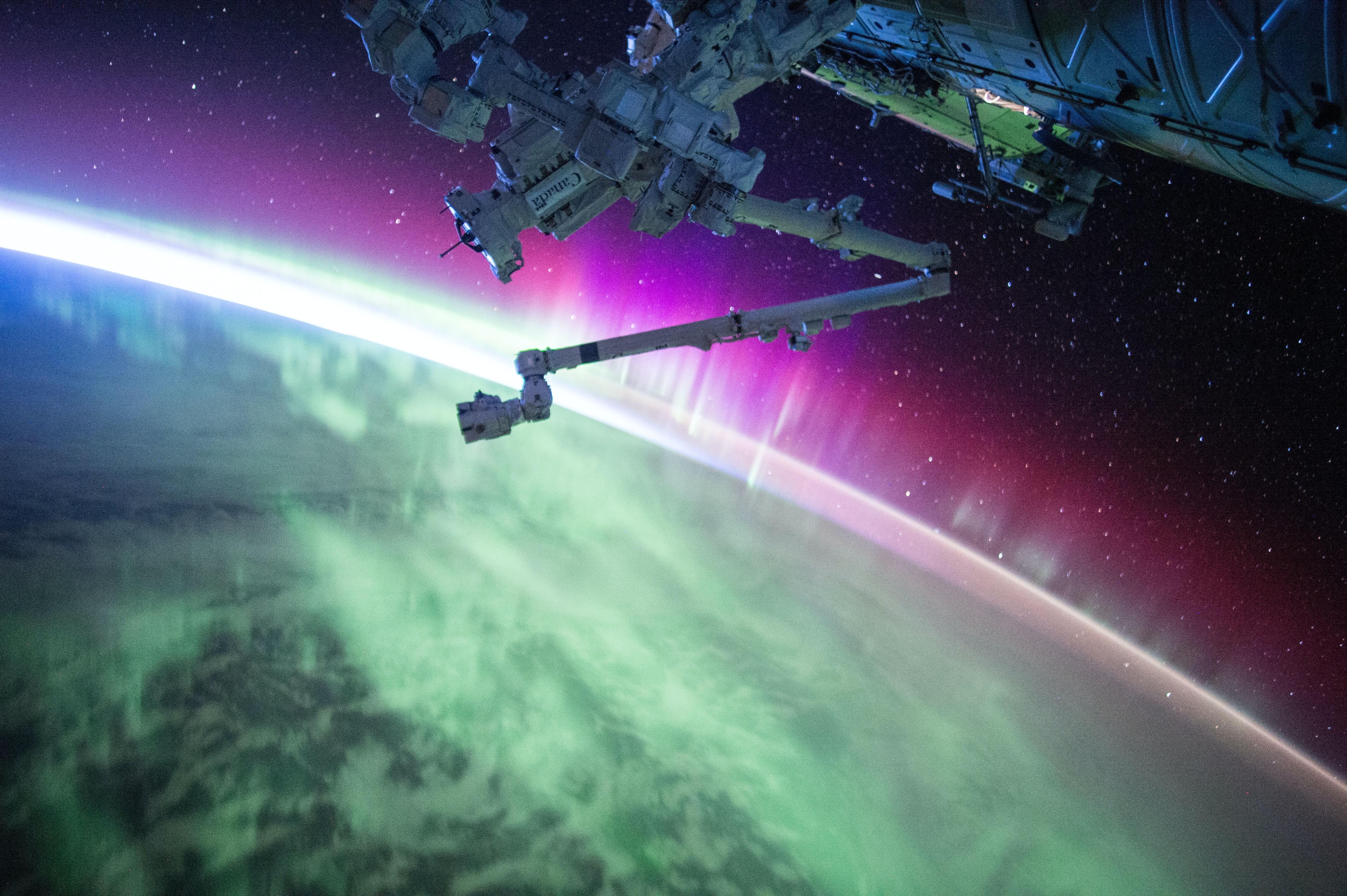 photography of purple and green aurora beam below grey space satellite