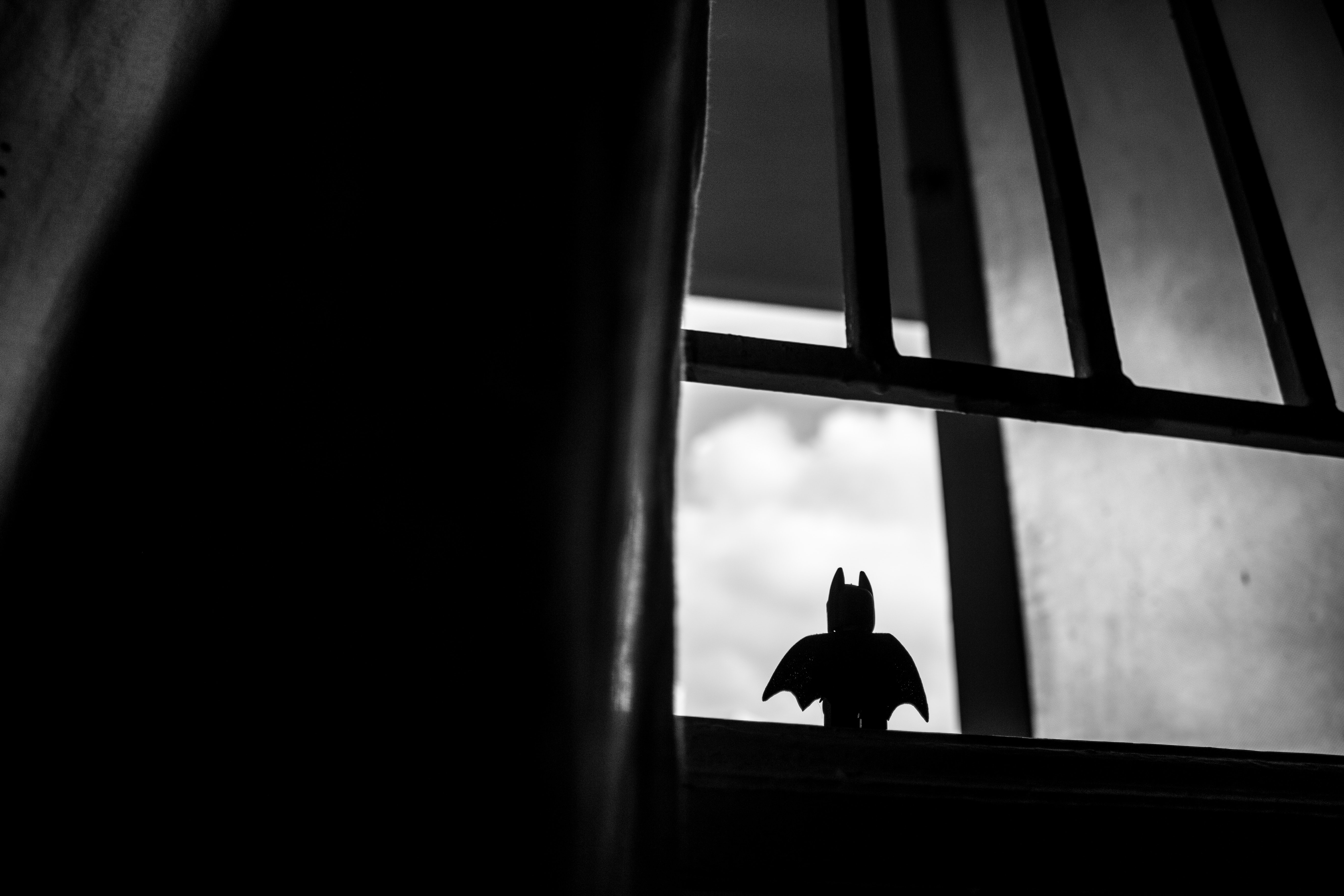 A Lego Batman toy sitting in a window looking out to the sky.