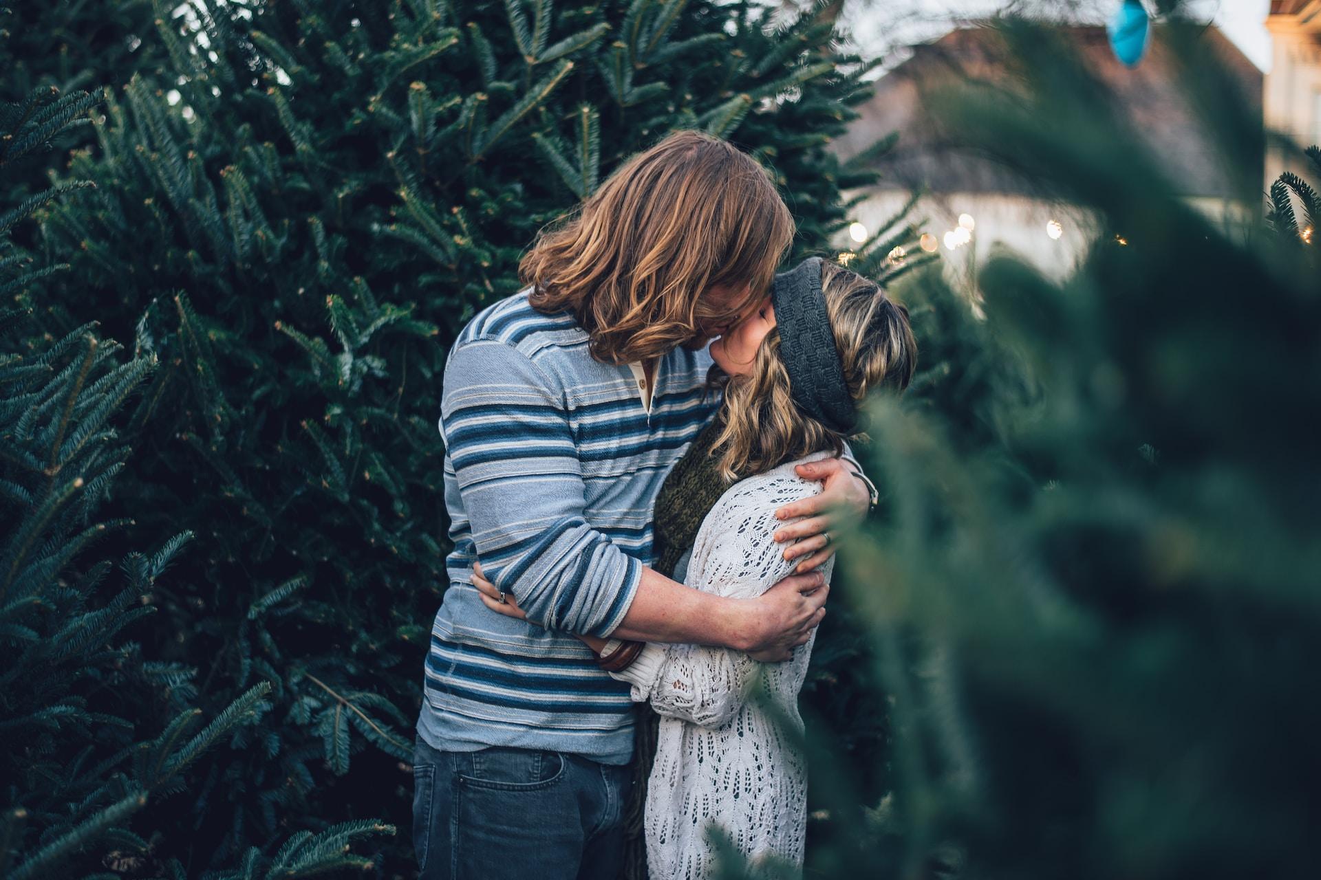 man kissing woman near pine tree