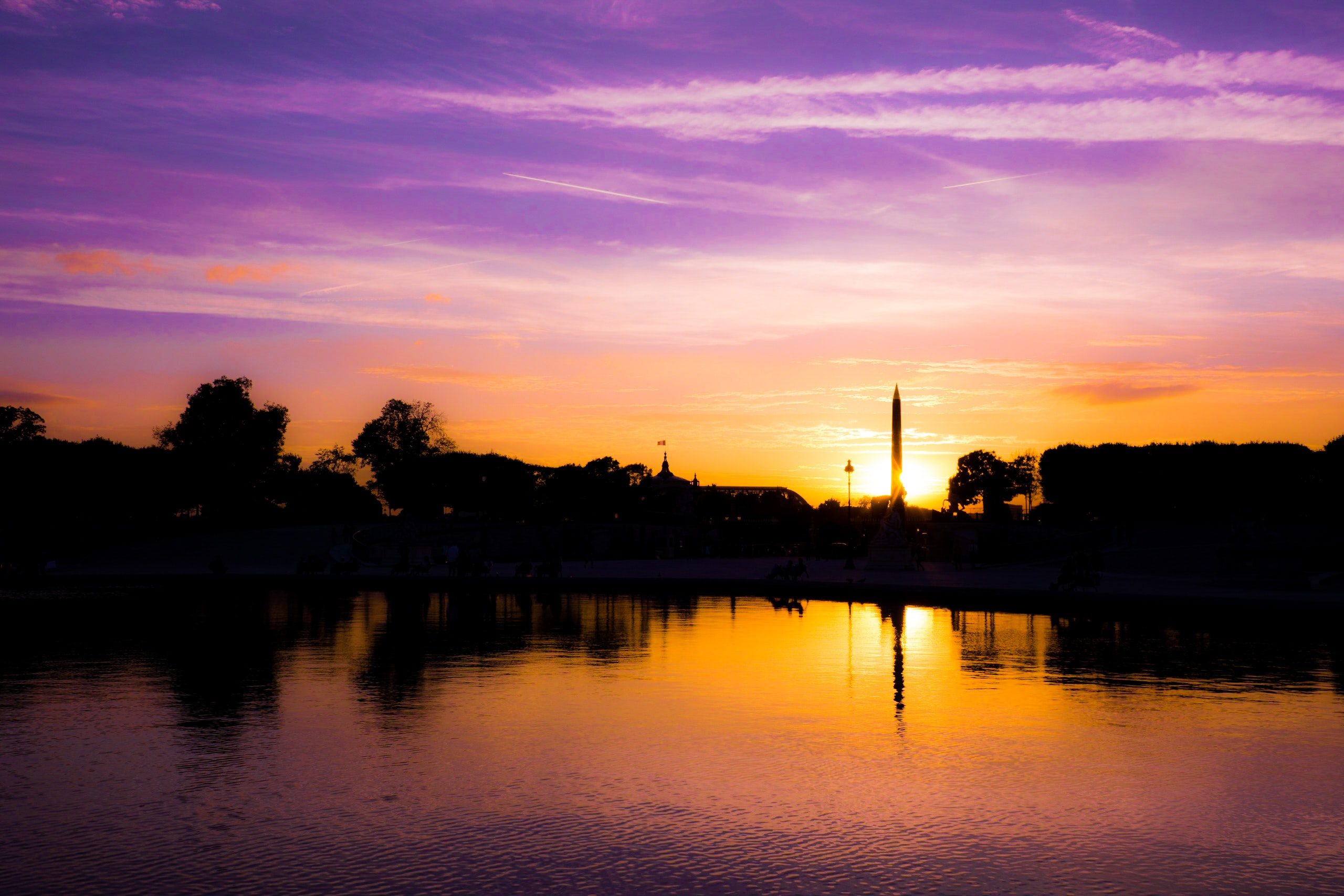 Colorful sunset and its reflection over a river with the silhouette of buildings.