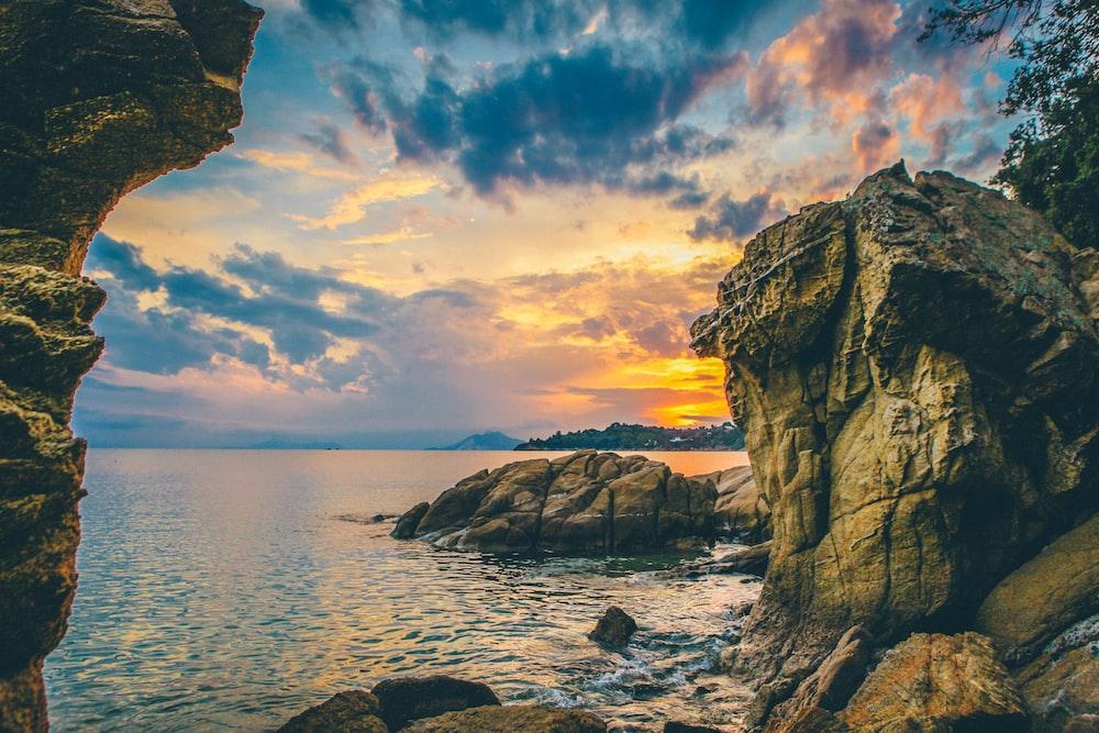 seashore near rocky mountain during golden hour