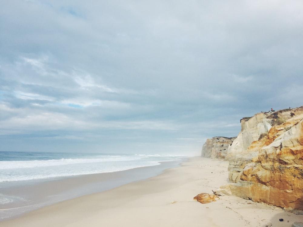 brown cliff beside ocean