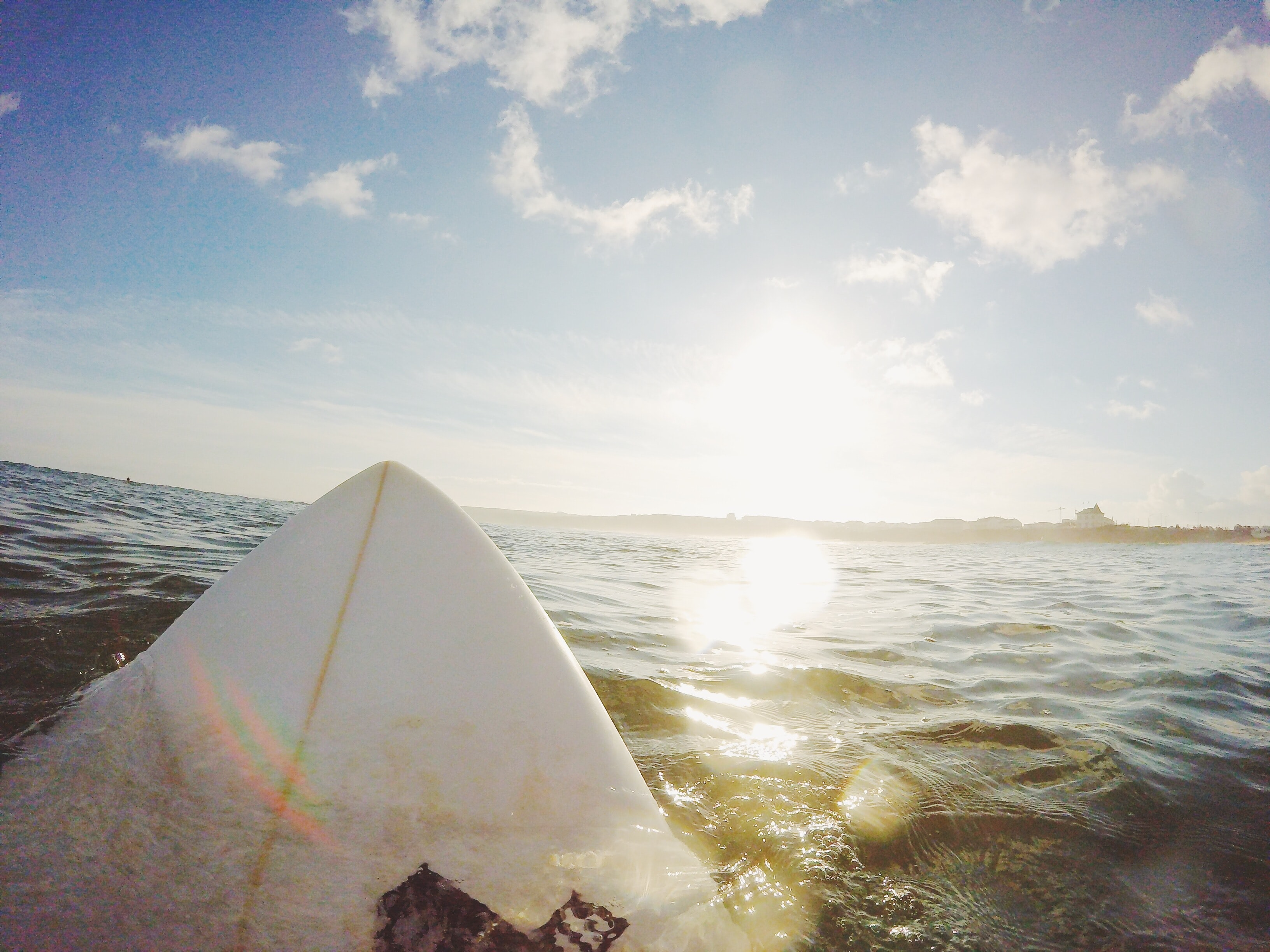 The front of a surfboard in the water facing the sun in Peniche