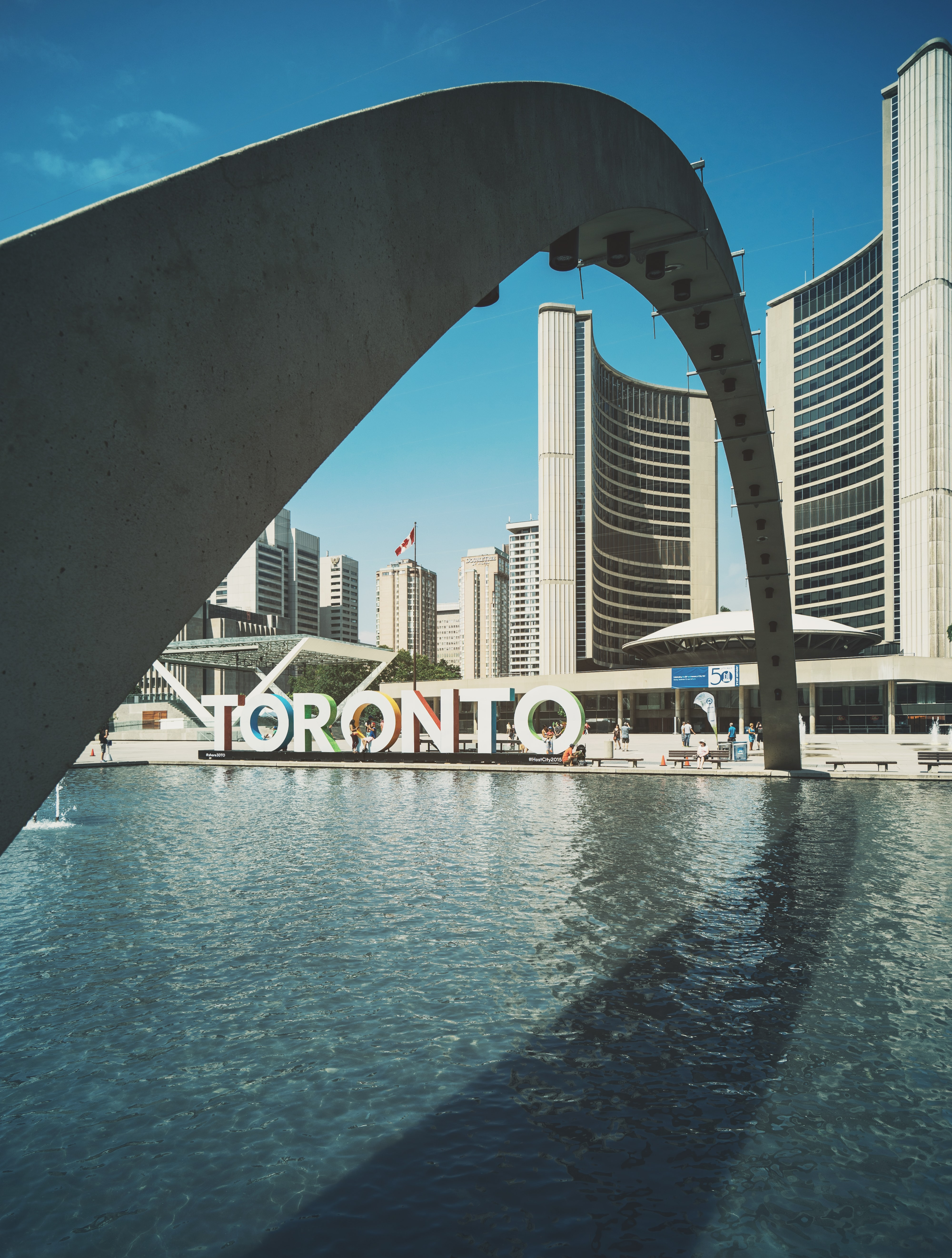 An arch over a fountain in an urban plaza in Toronto