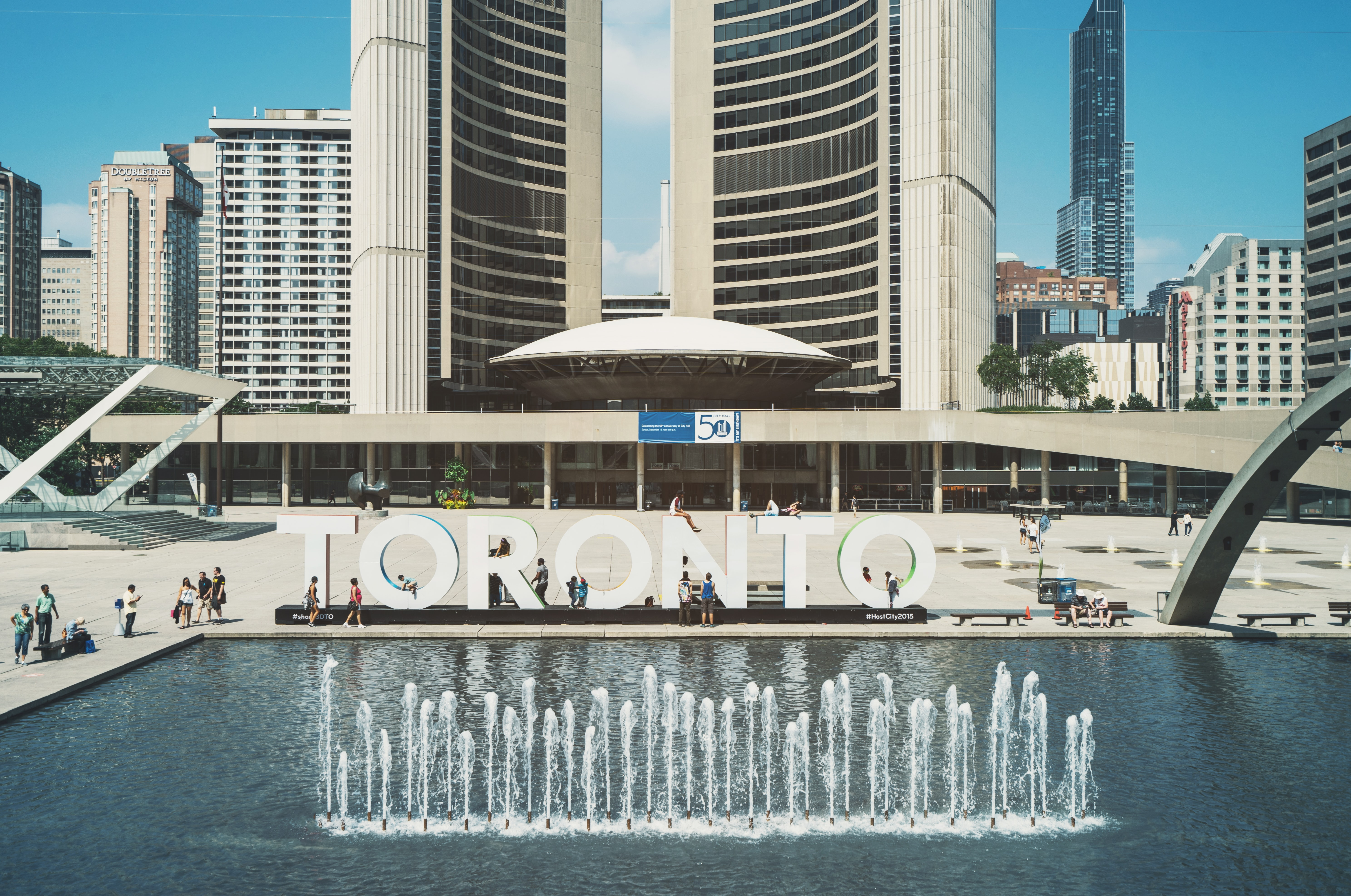 """Large letters spell out """"Toronto"""" next to a fountain in an urban plaza"""