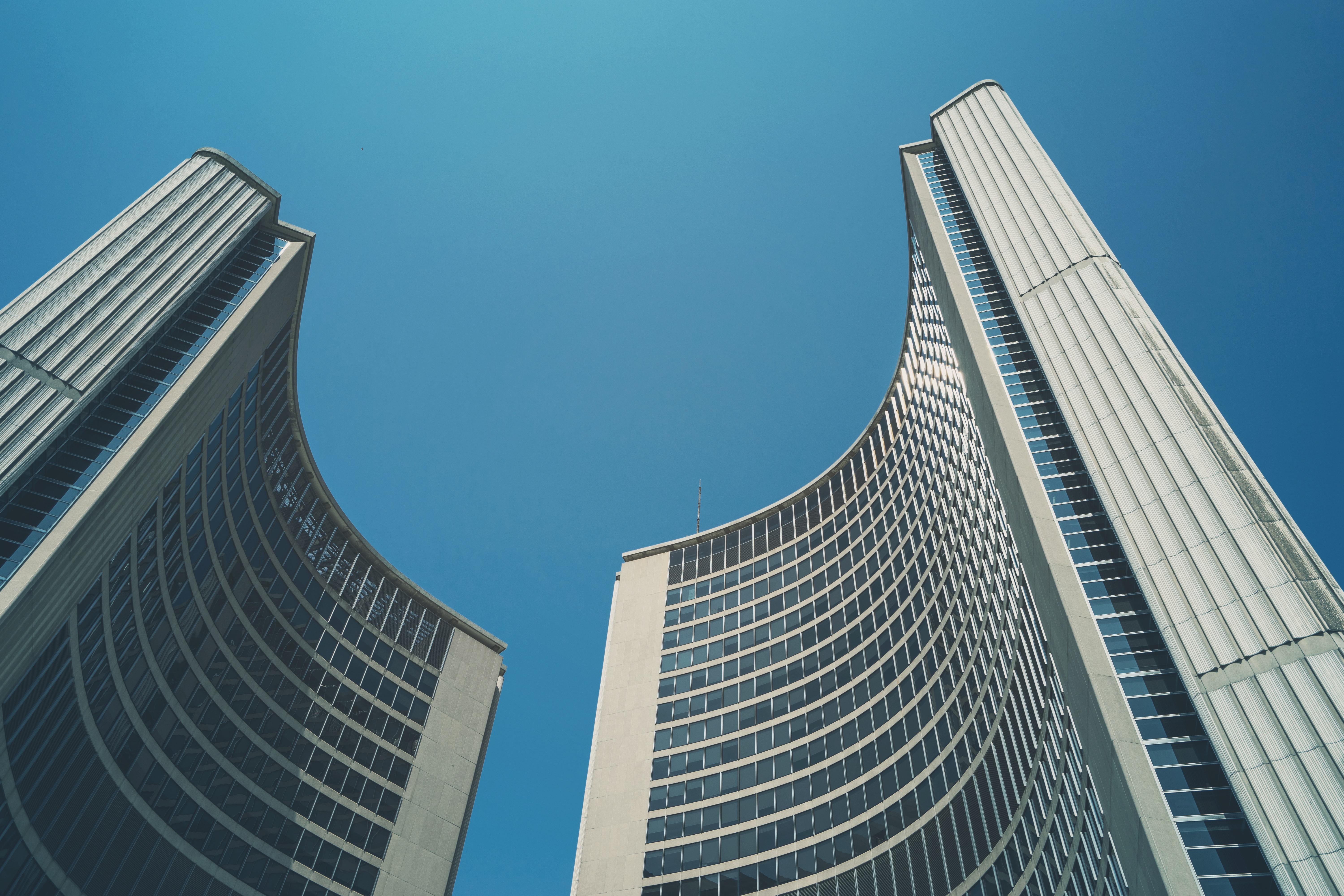 Two curved towers of Toronto City Hall under a blue sky