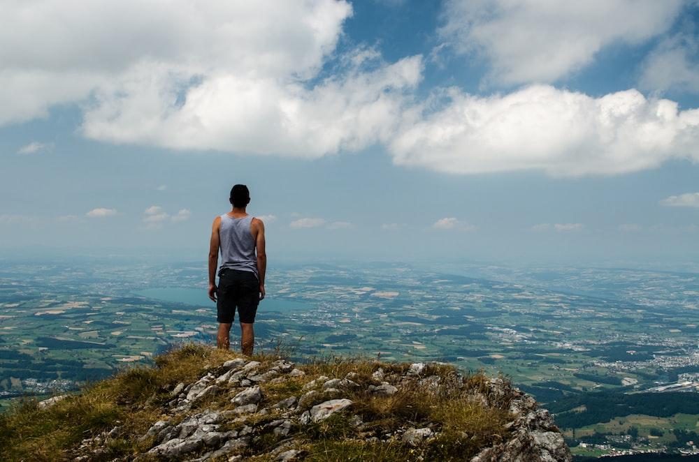 man standing at peak of mountain