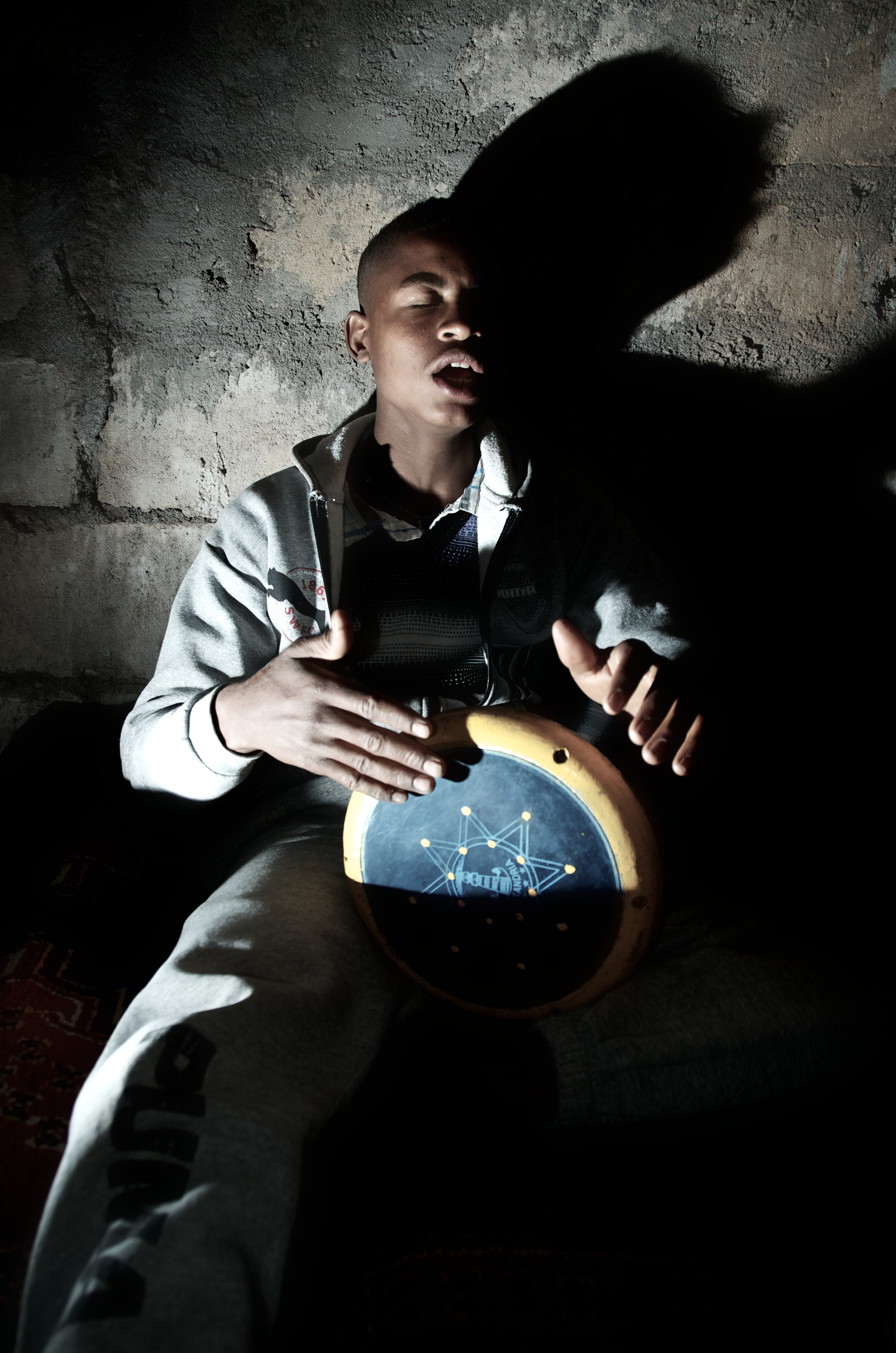 A man seated against a bare brick wall and playing a drum