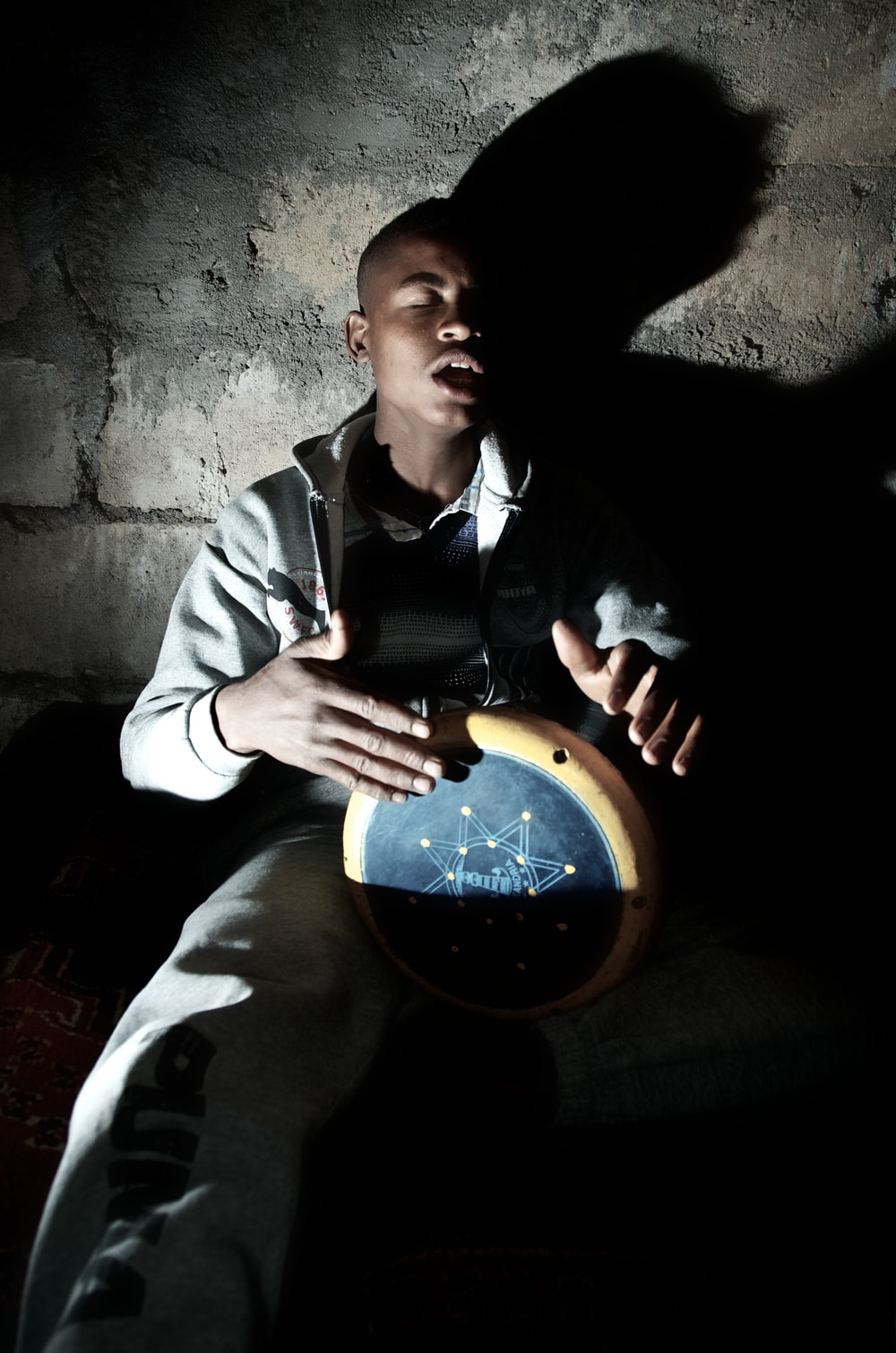 man playing percussion instrument near wall