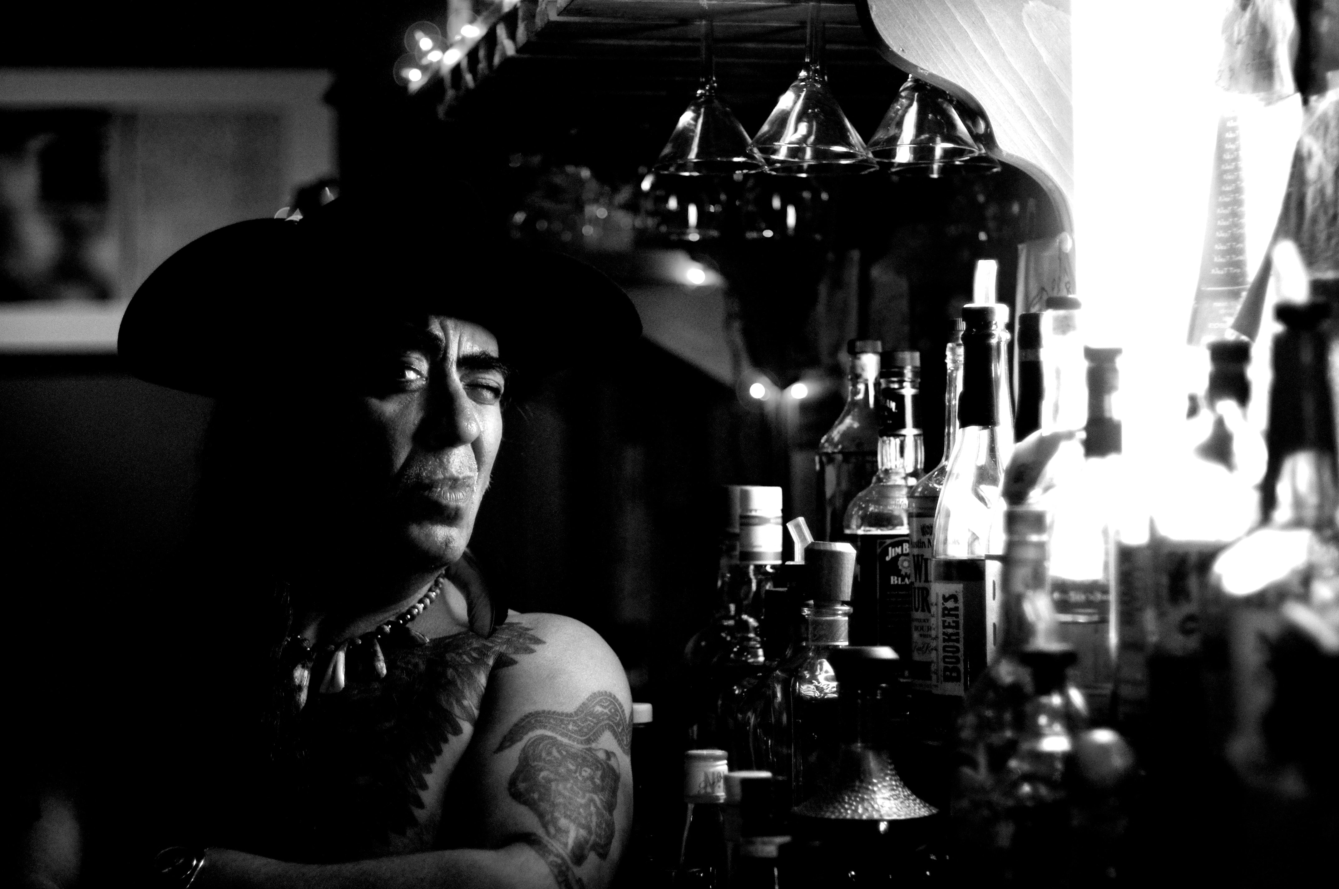 Black and white image of a tattooed man sitting next to bottles of alcohol at Rite Spot Cafe