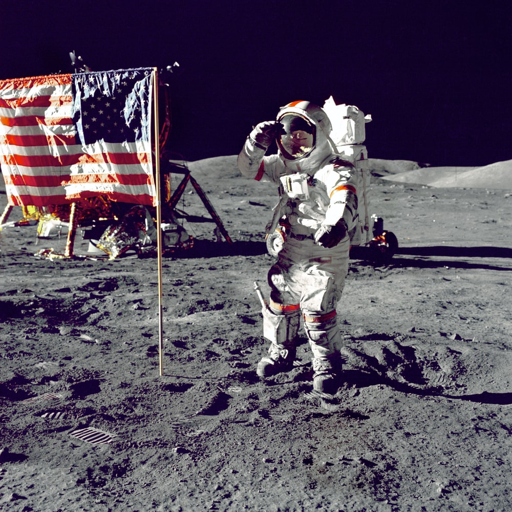 astronaut standing on moon beside U.S.A. flag