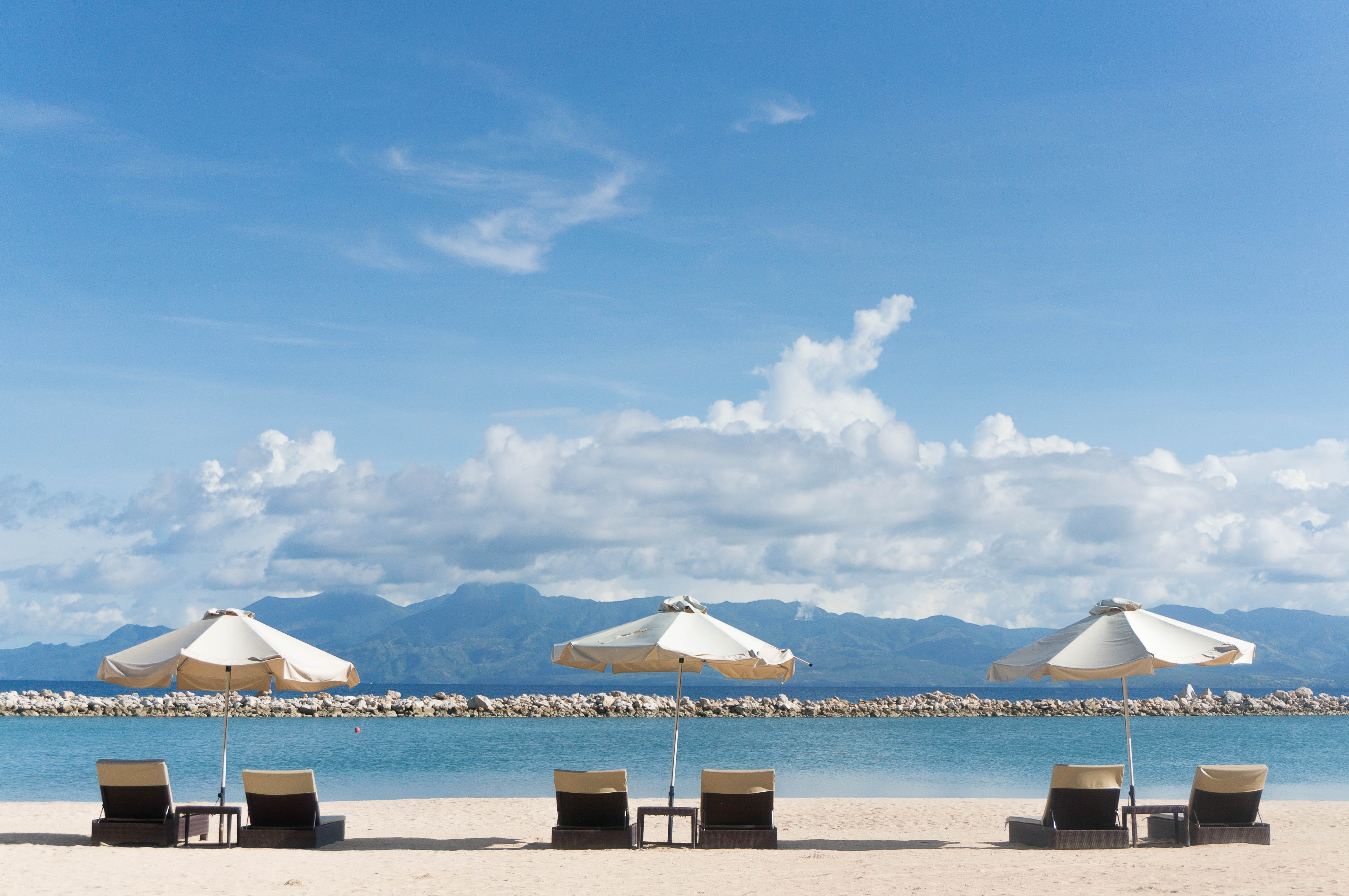Deck chairs under umbrellas on a sunny beach with view on tall hills