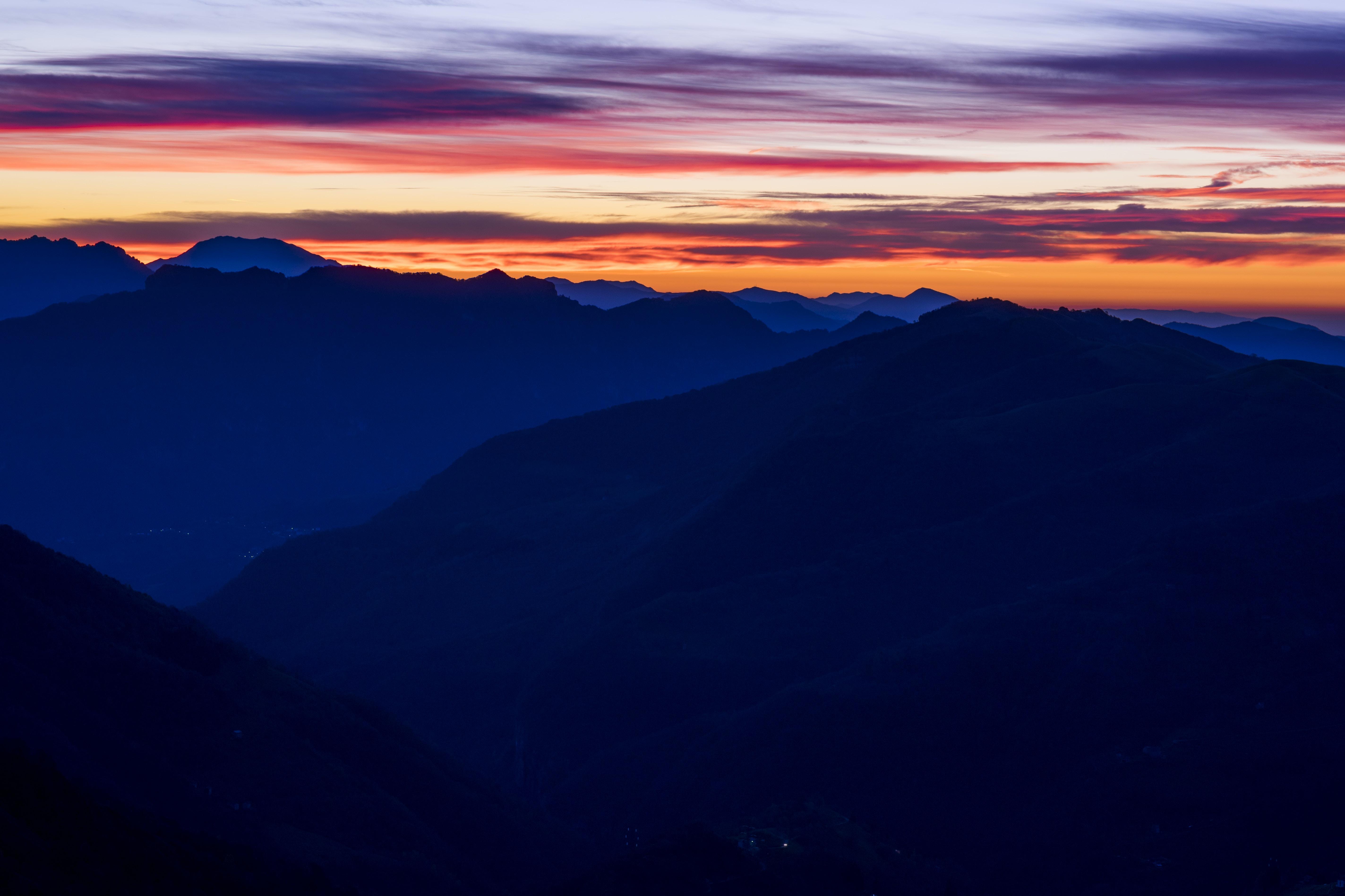 mountain ranges under orange sky during sunset