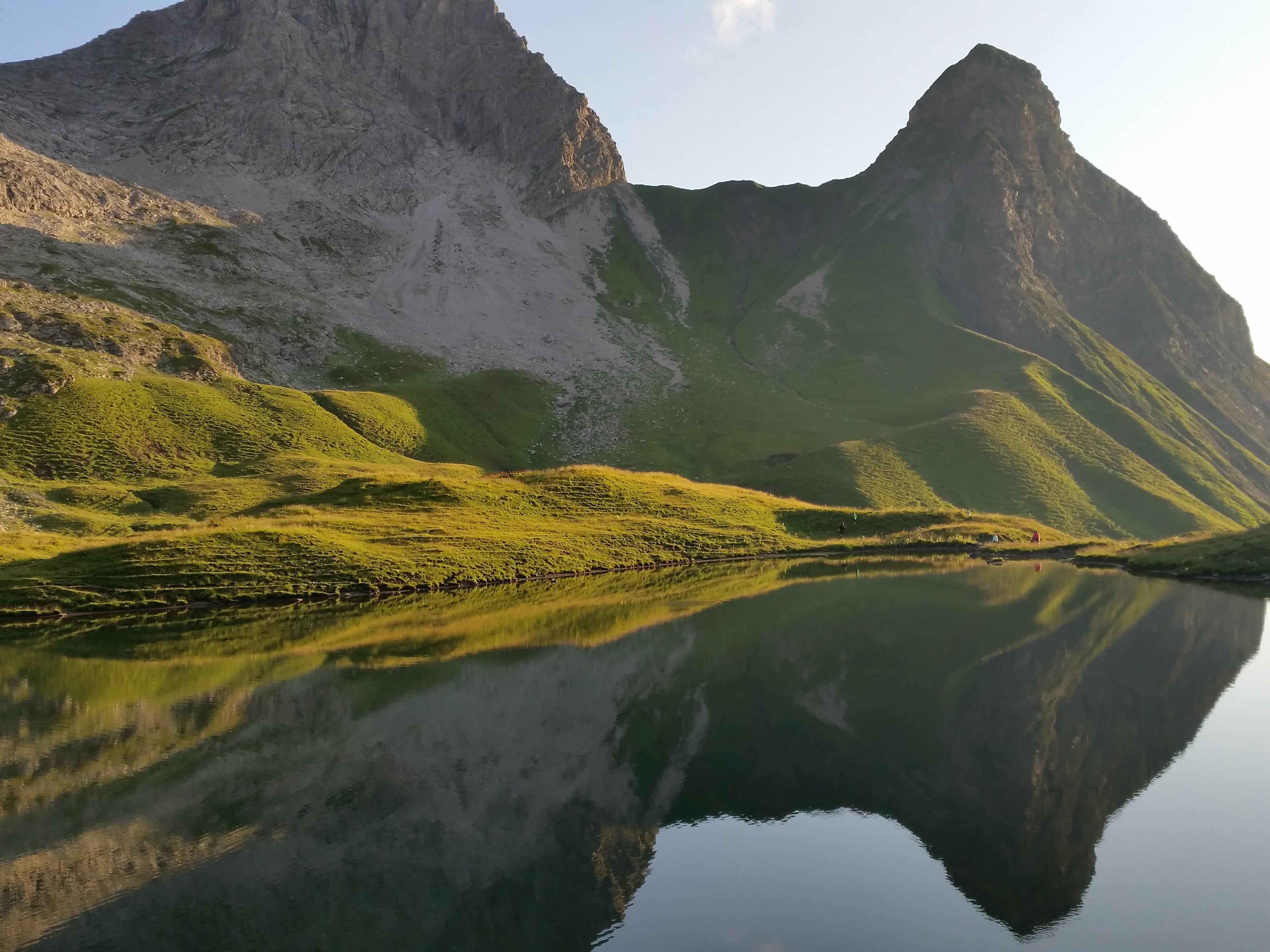 green mountain near lake under white cloudy sky
