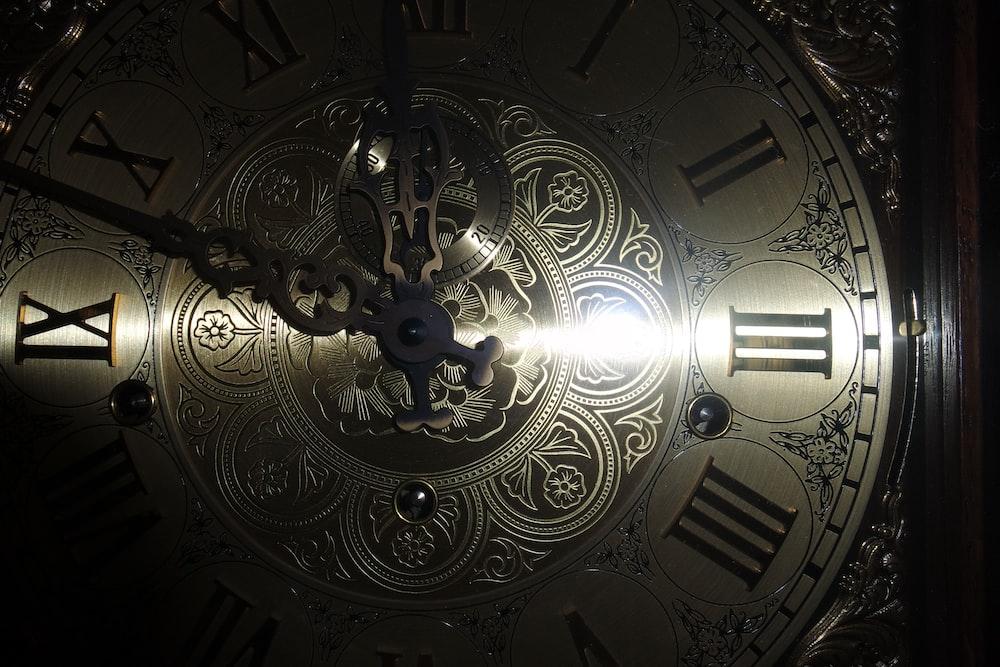 brass-colored analog clock