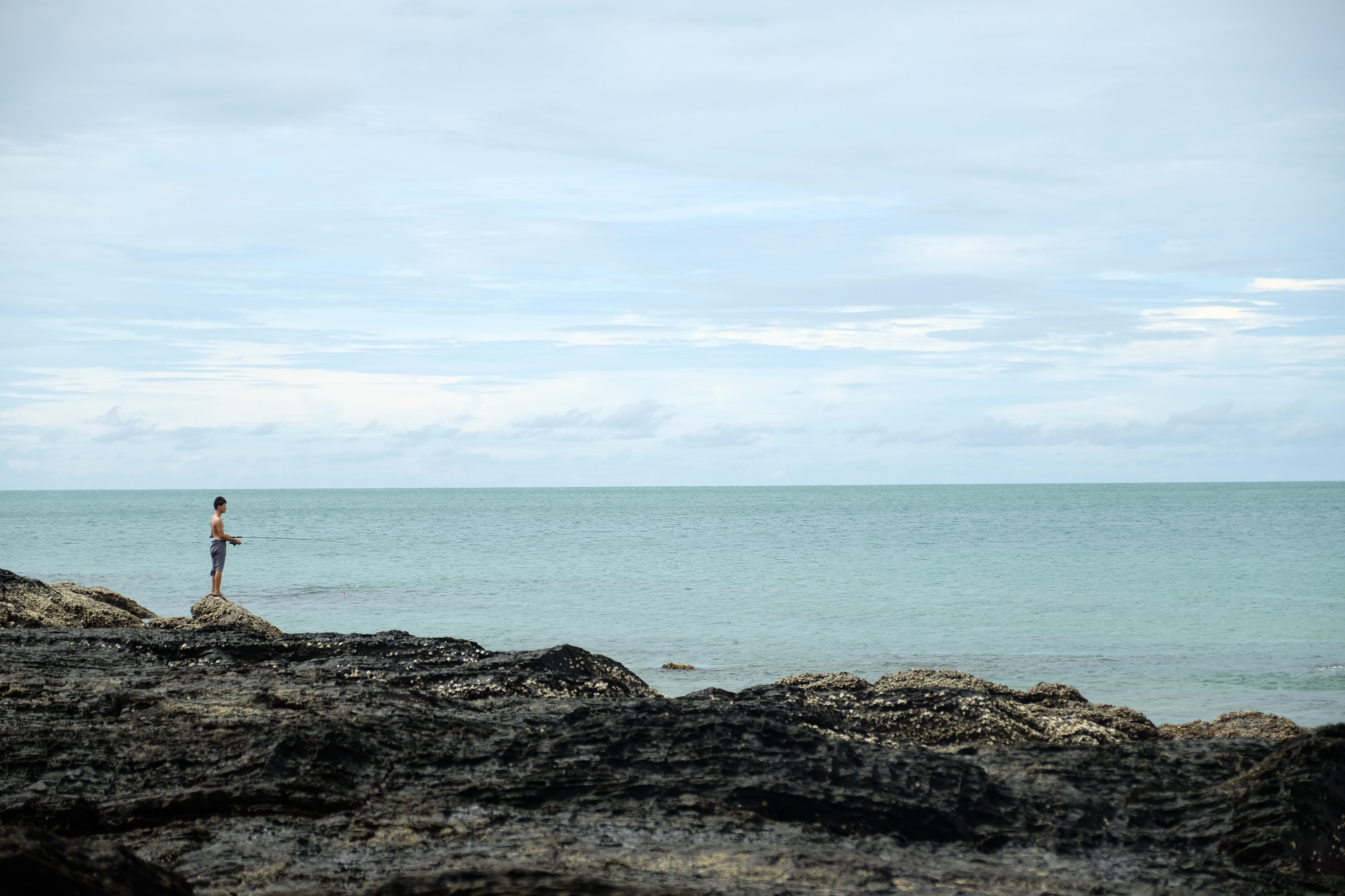 man standing on cliff fronting calm body of water