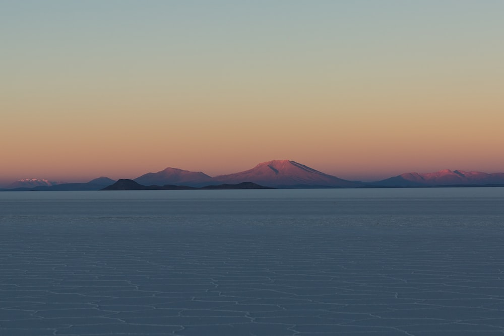 body of water and brown mountains under orange skies during sunset
